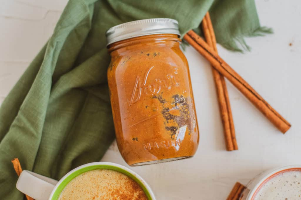 Low carb Pumpkin Spice Syrup in a glass jar, with cinnamon sticks on the side and a green napkin in the back.