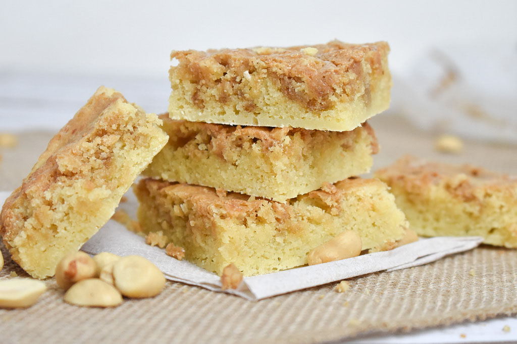 Low carb peanut butter swirl blondies with peanuts on a brown cloth