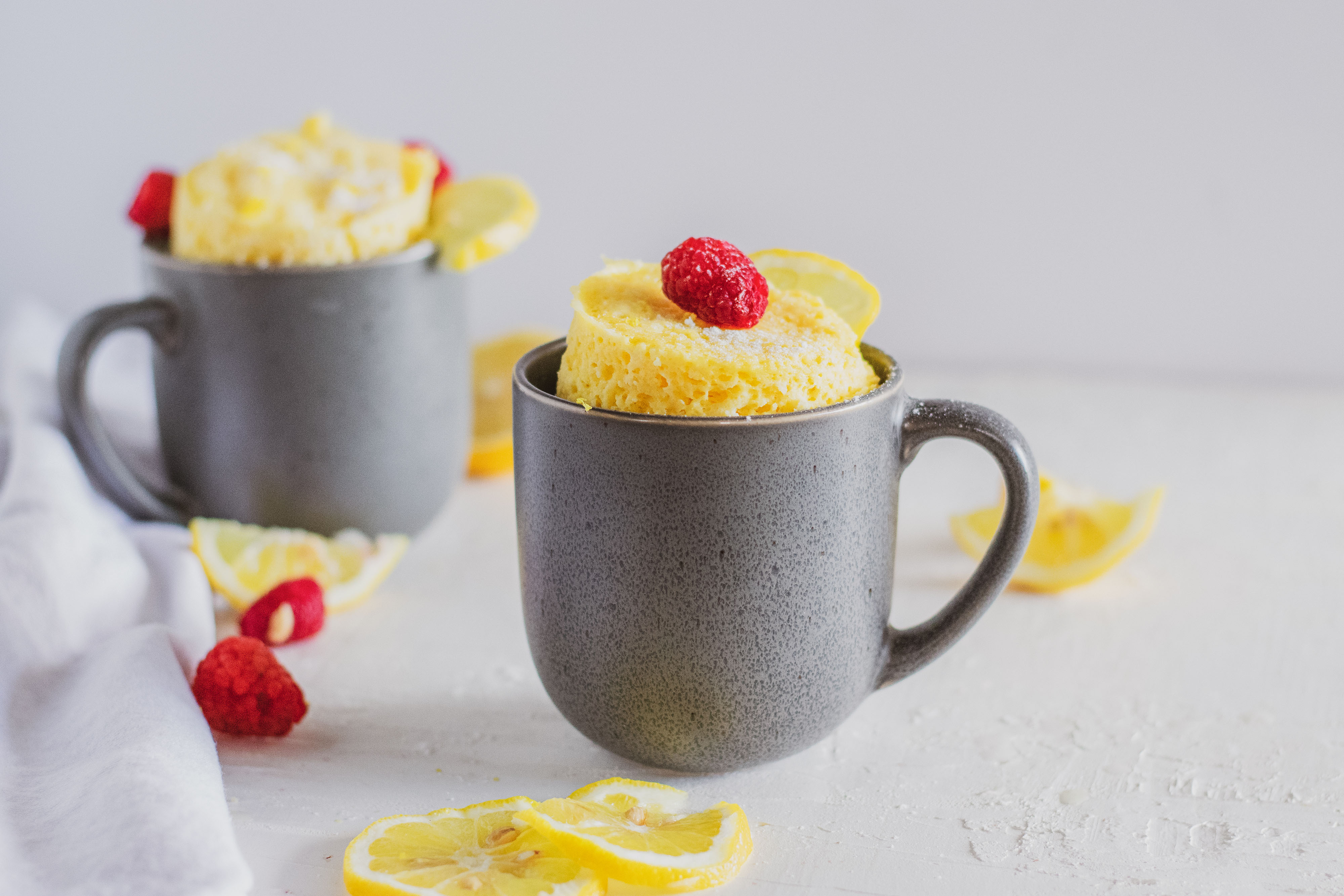 Low carb lemon mug cakes in a grey mug with raspberries and lemon slices on a white surface.
