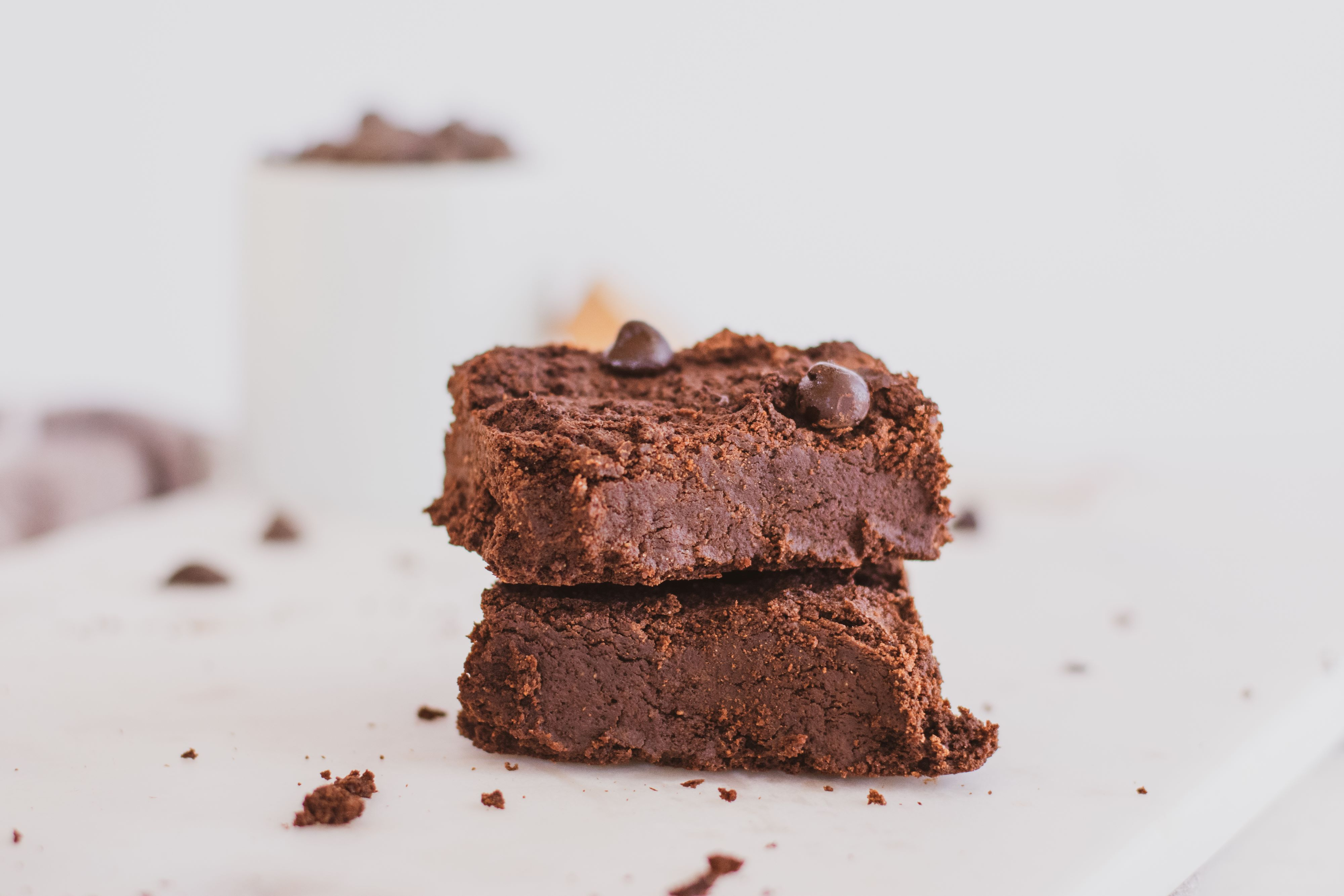Keto Avocado Brownies with chocolate chips on top. Set on a white surface.