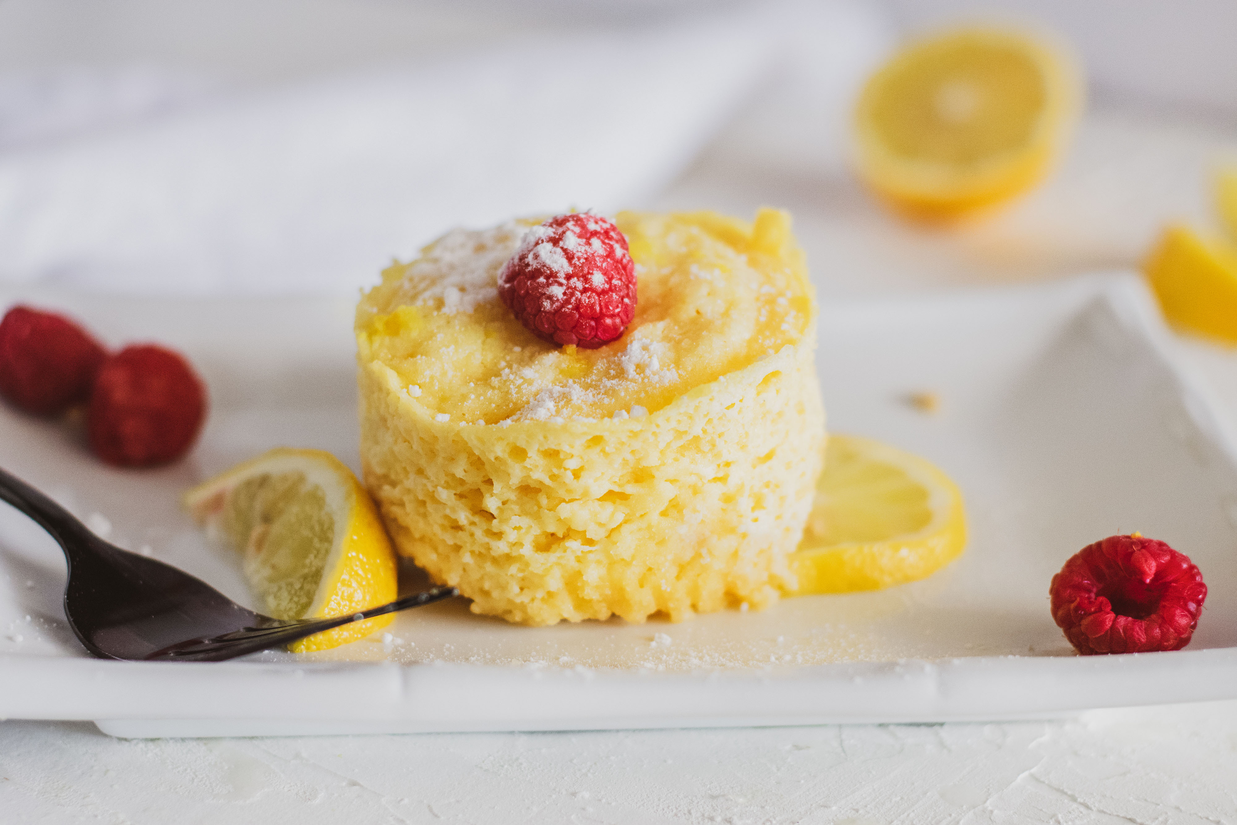 Low carb lemon mug cakes on a white plate with raspberries and lemon slices on a white surface.