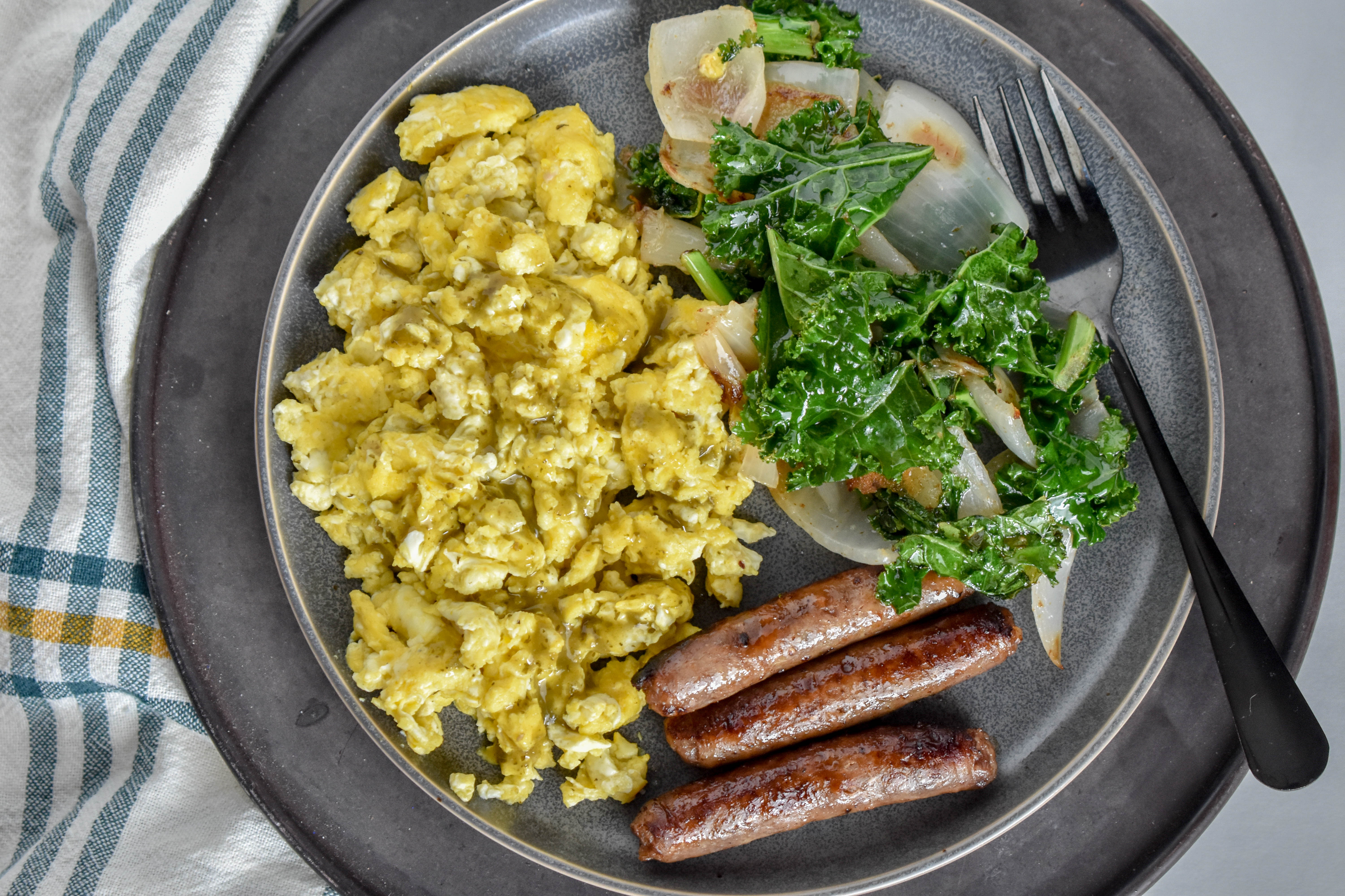 Clean Eating Breakfast with scrambled eggs, sausage links and sauteed kale and onions on a grey plate.