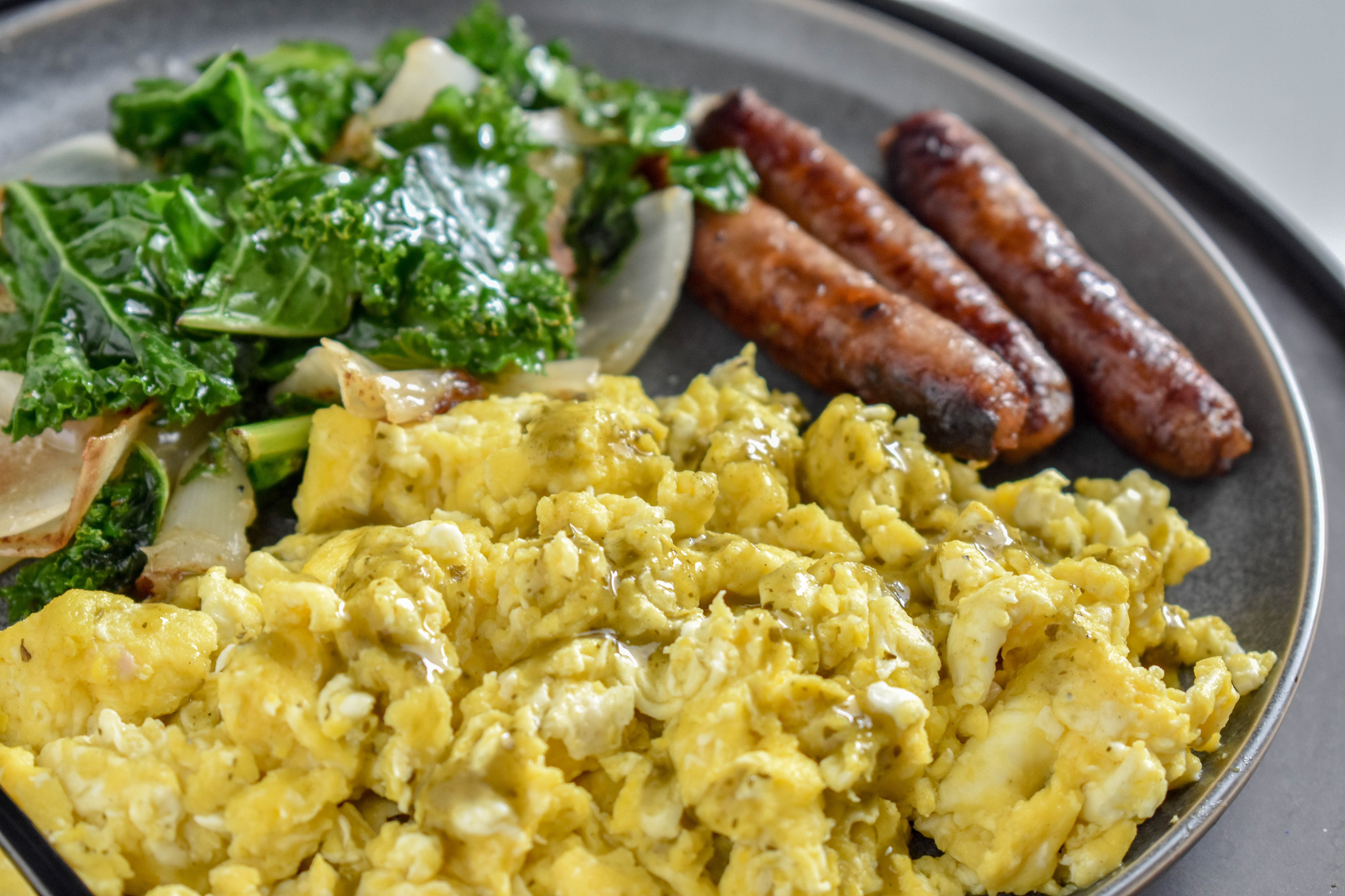 Scrambled eggs with sausage links and a side of sauteed onions and kale sitting on a dark grey plate.