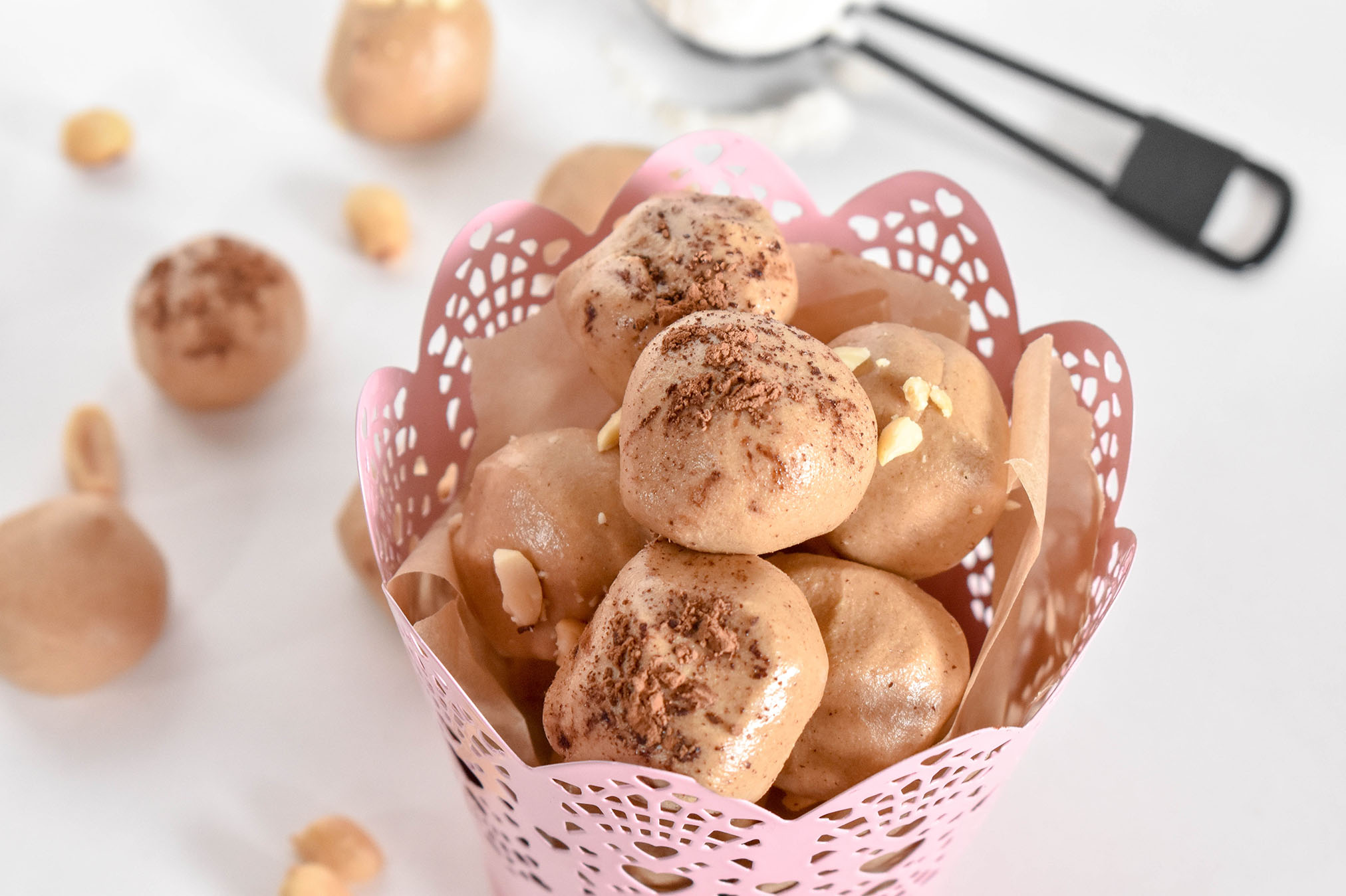 Peanut butter protein balls in a pink decorative cup on a white surface.