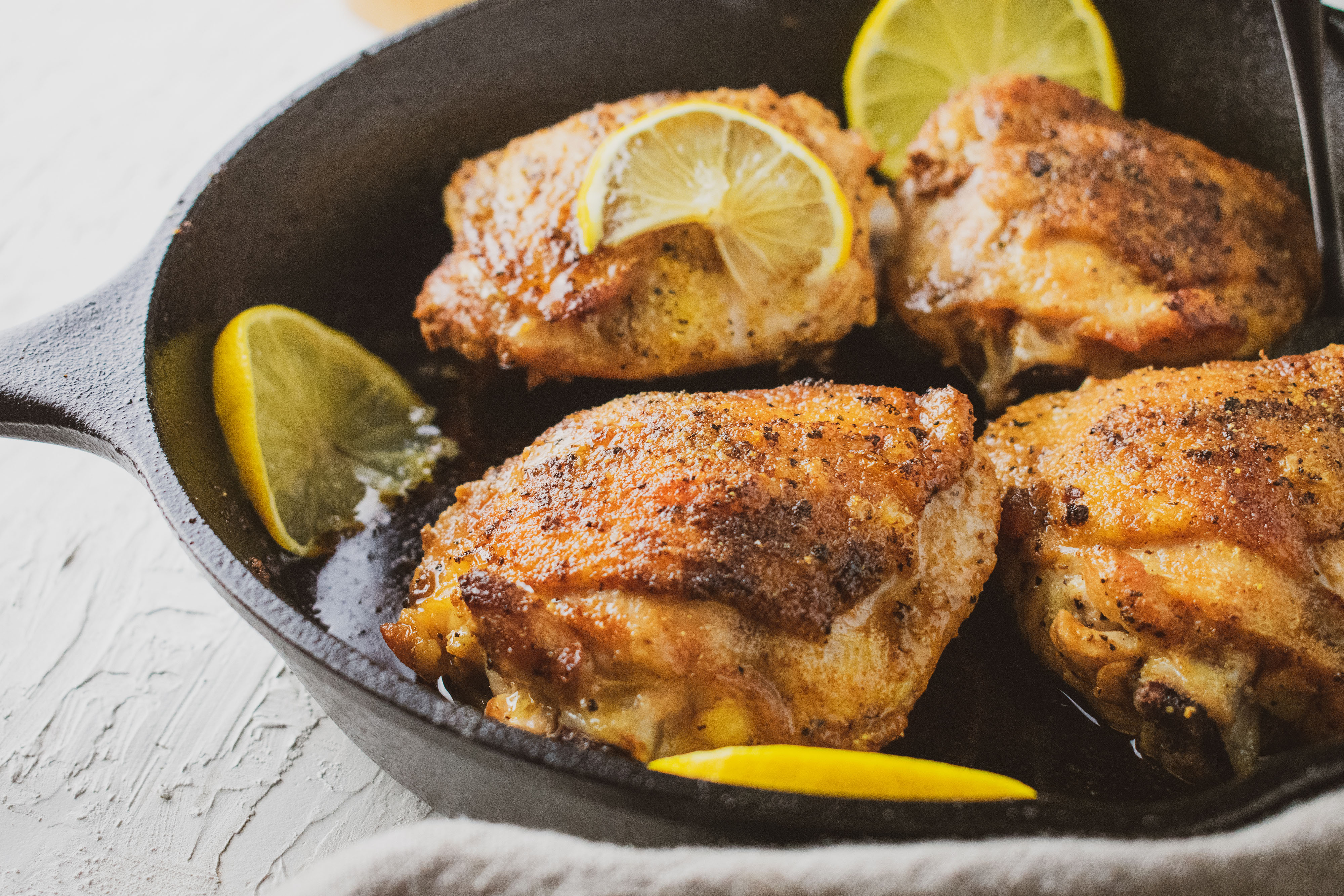 Low carb crispy chicken thighs with lemons in a cast iron skillet seasoned with lemon pepper.