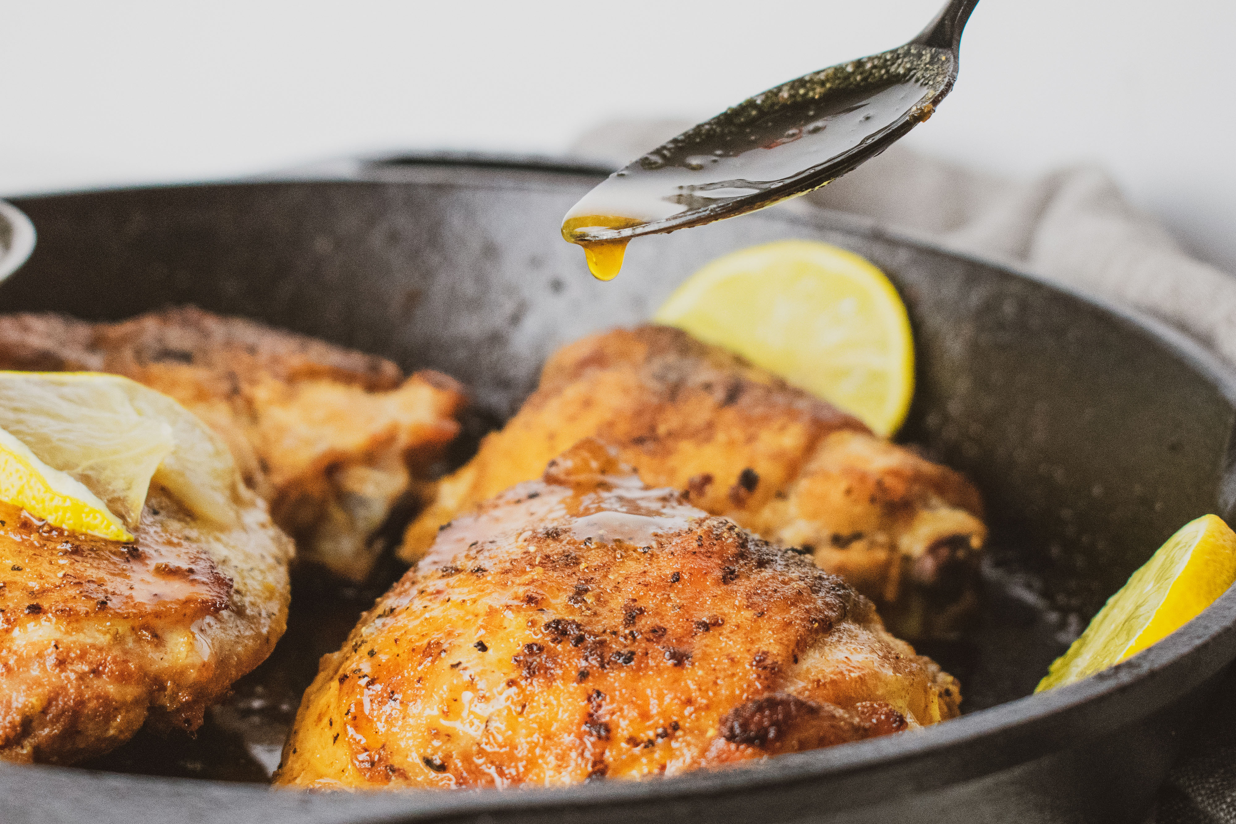 Low carb crispy chicken thighs with lemons in a cast iron skillet seasoned with lemon pepper. With a spoon pour juice over the chicken.