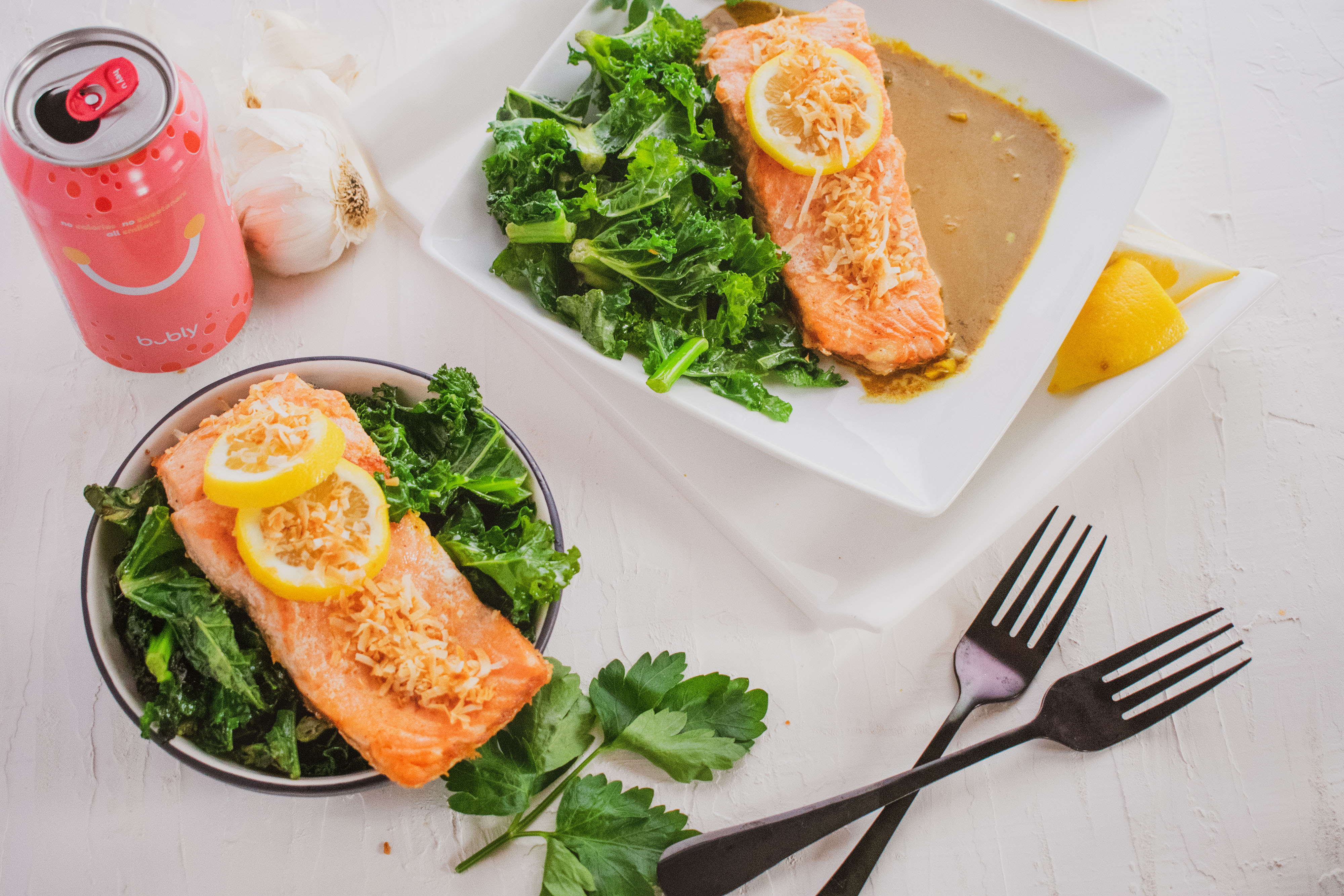 Salmon filet in curry and and kale salad on the side on a white surface