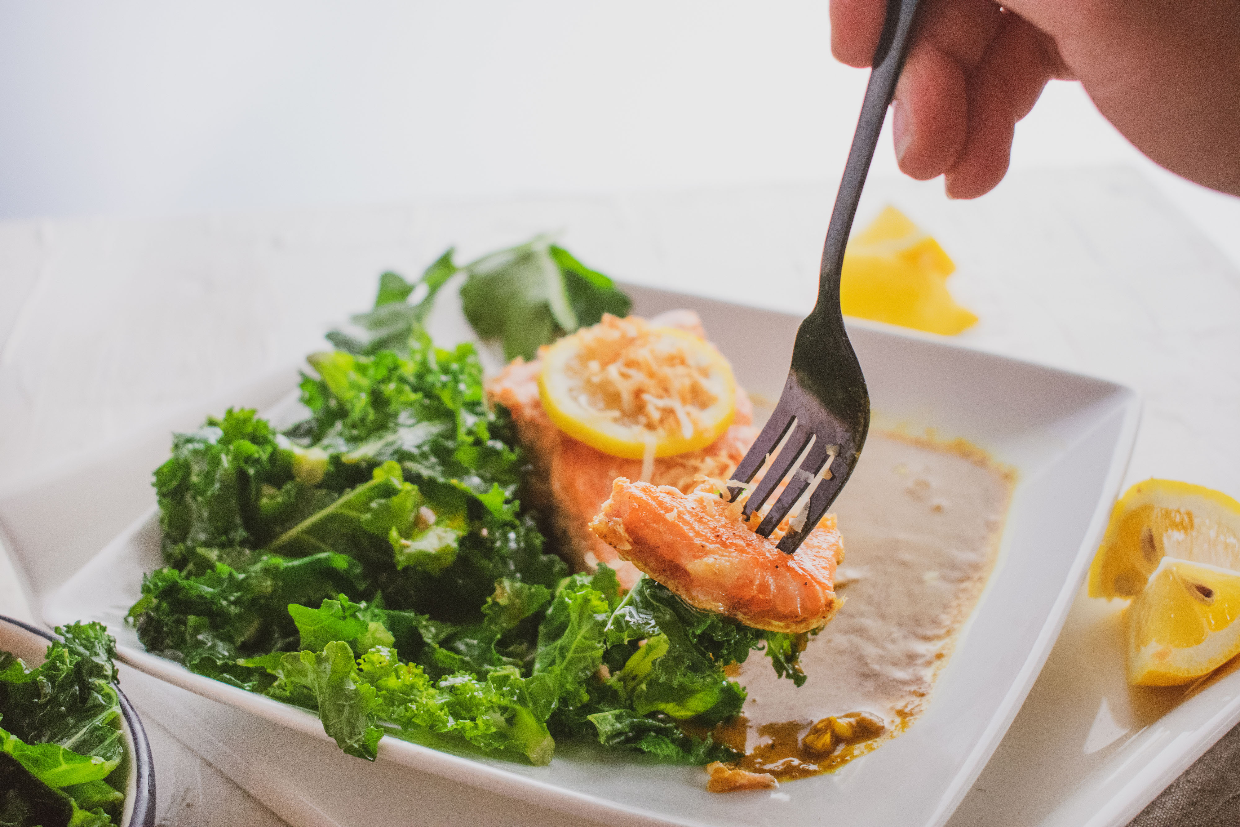 Salmon filet in curry and and kale salad on the side on a white surface with a fork scooping up a bite