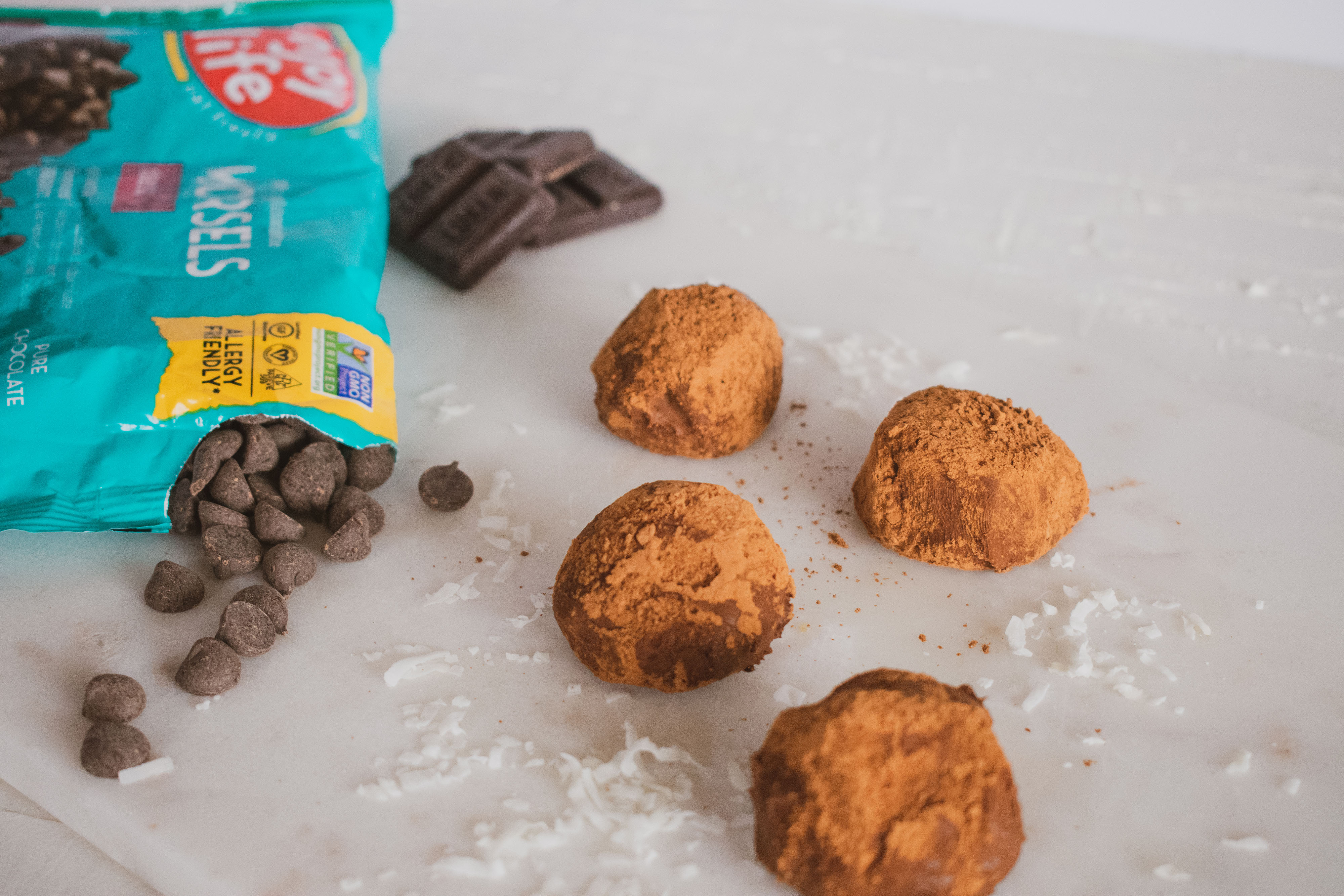 Cocoa powder covered keto chocolate truffles. Set on a white surface with a bag of Enjoy Life in the background.