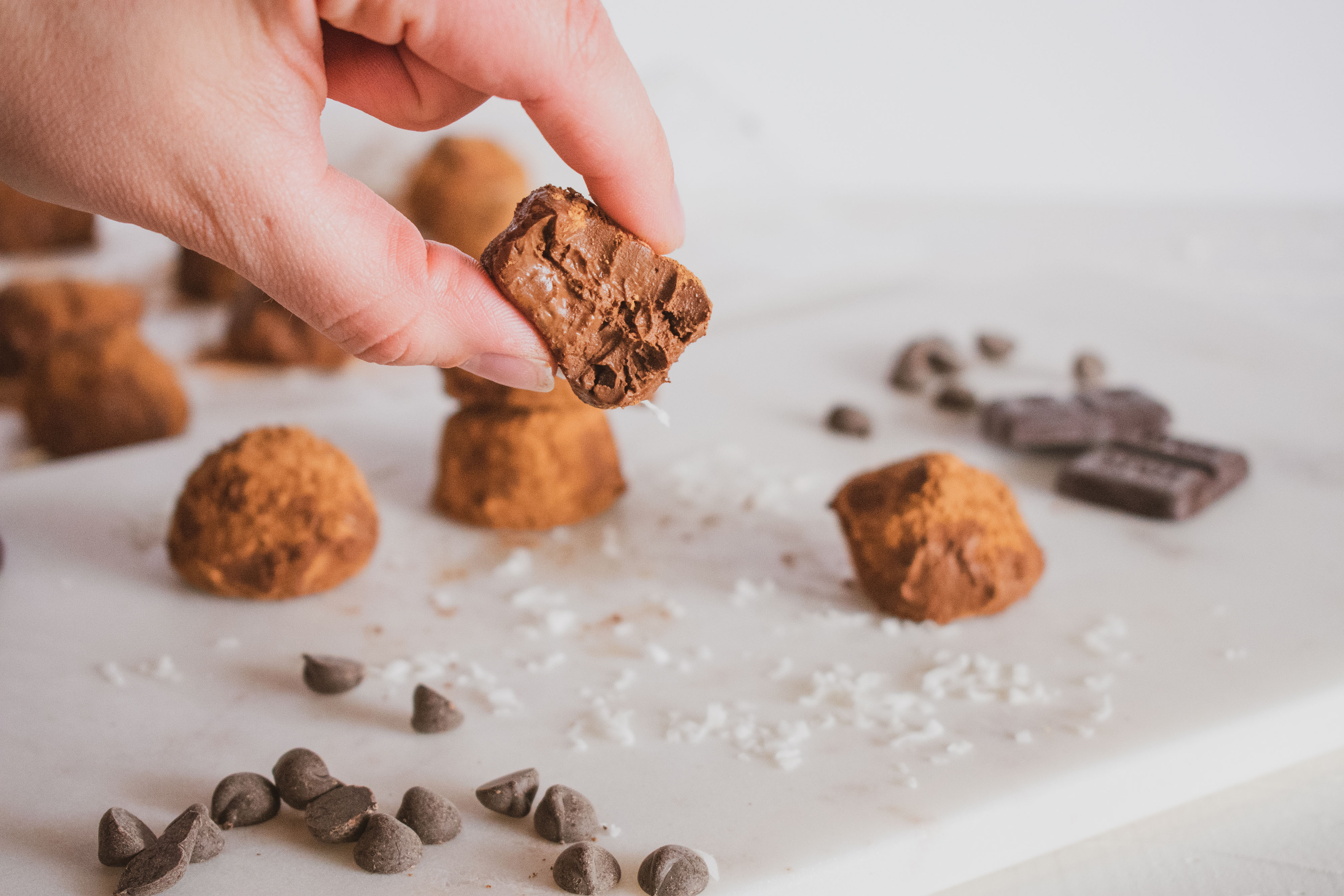 Cocoa powder covered keto chocolate truffles. Set on a white surface with chocolate chips and with a bite taken out.