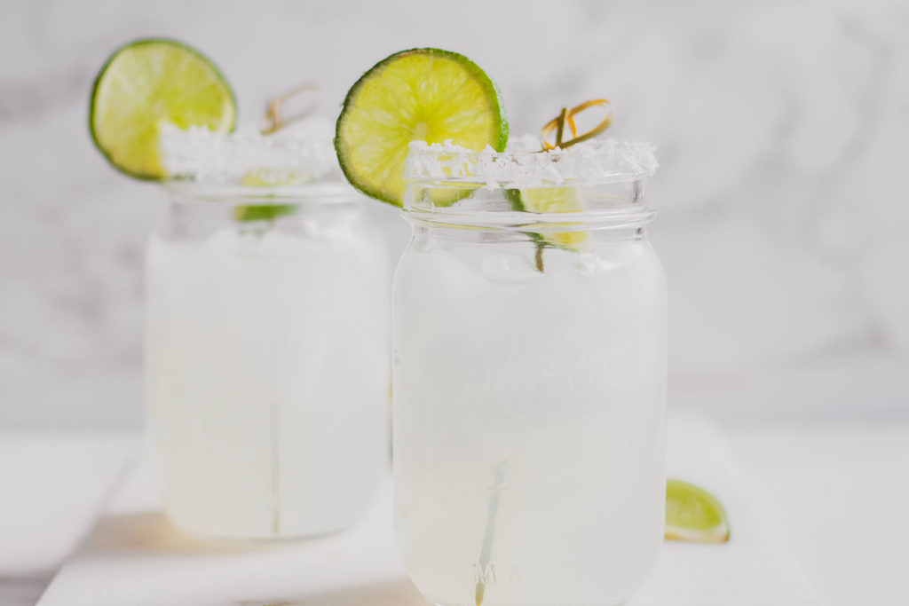Keto margarita in a mason jar with salt and a sliced lime on the rim on a white surface.
