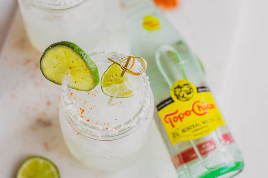 Keto margarita in a mason jar with salt and a sliced lime on the rim on a white surface with a topo chico on the side.