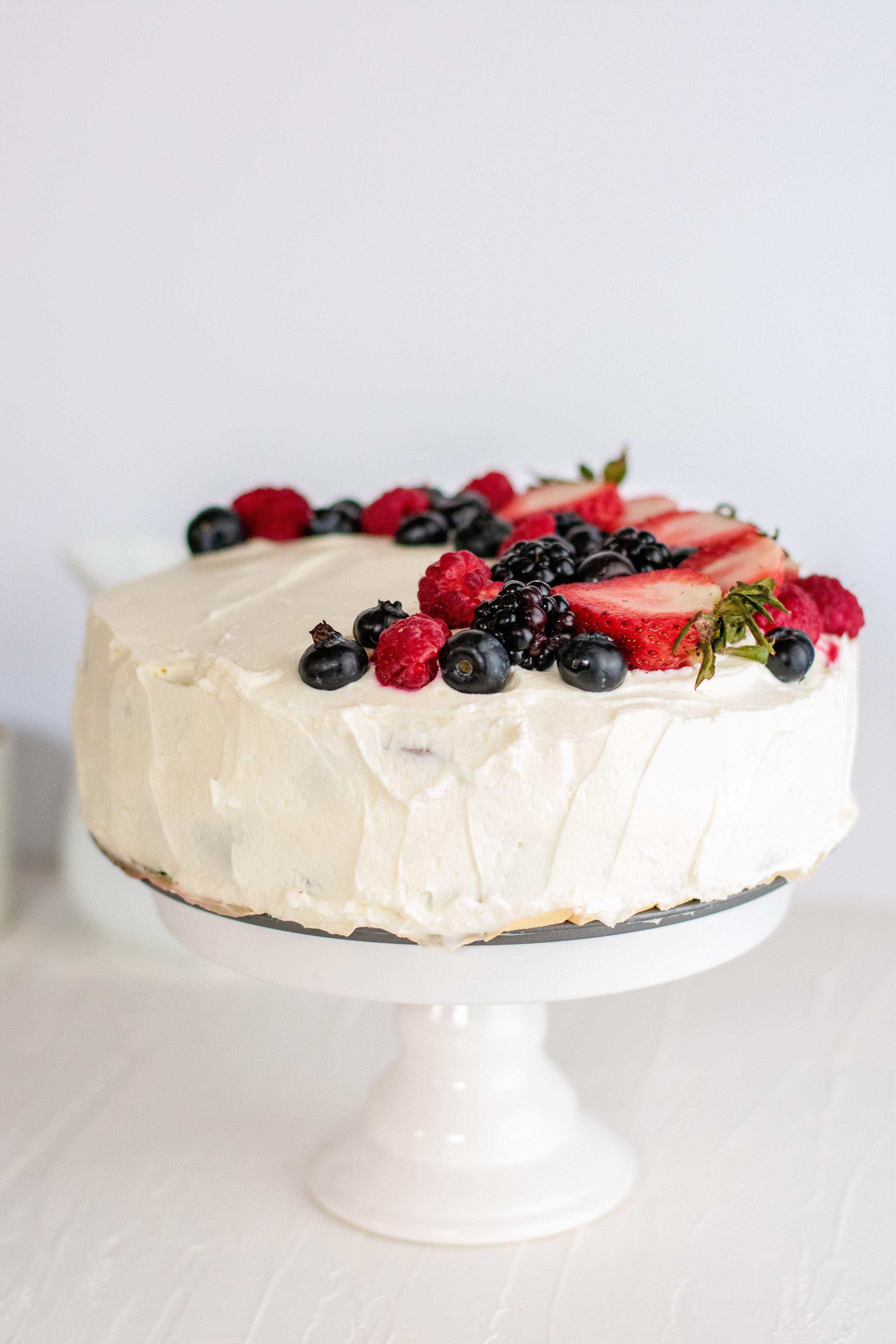 Keto Chantilly Cake a white cake with berries covering the top on a cake stand with a white background