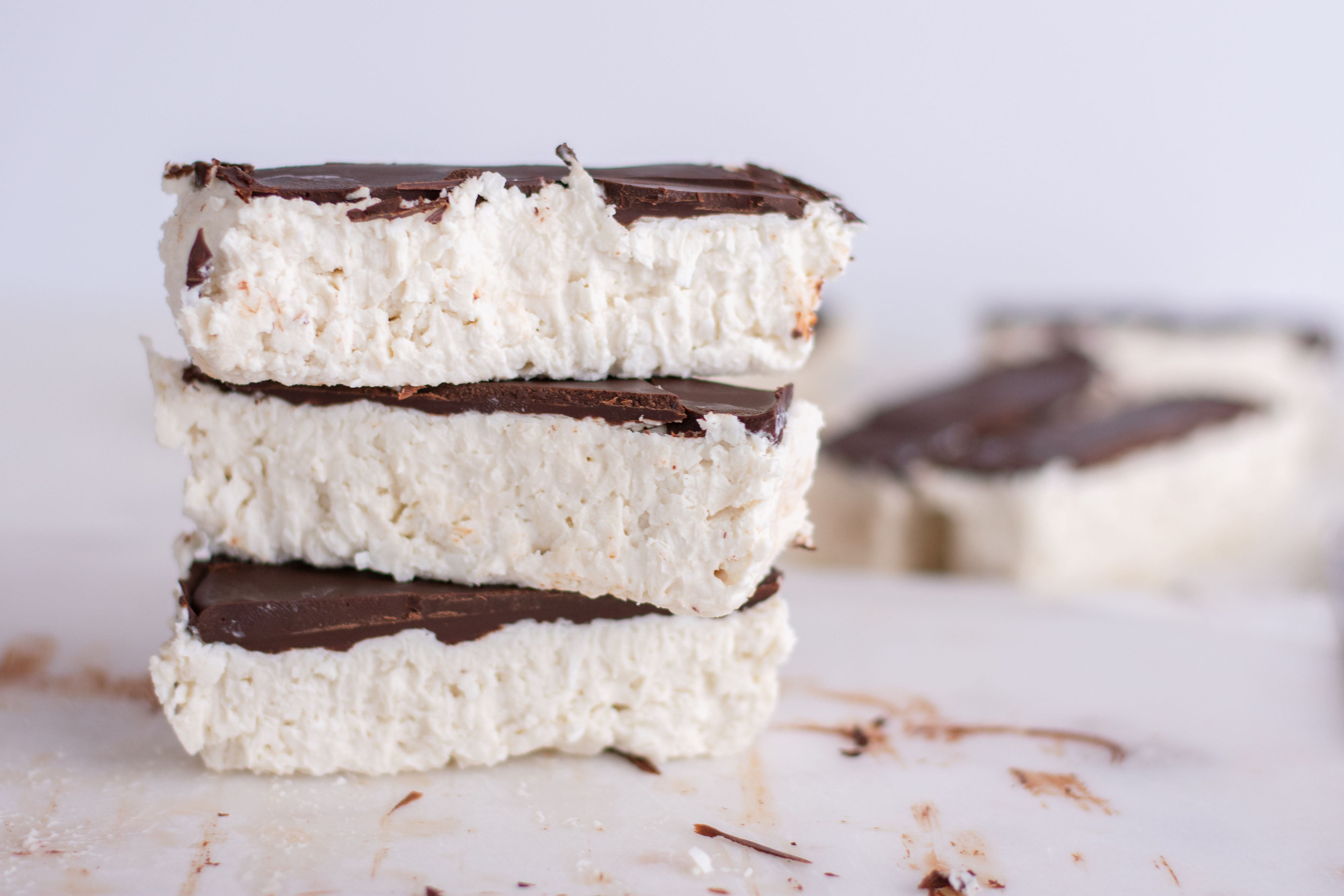 White coconut bars with a chocolate layer on top. Staked on top of each other on a white surface
