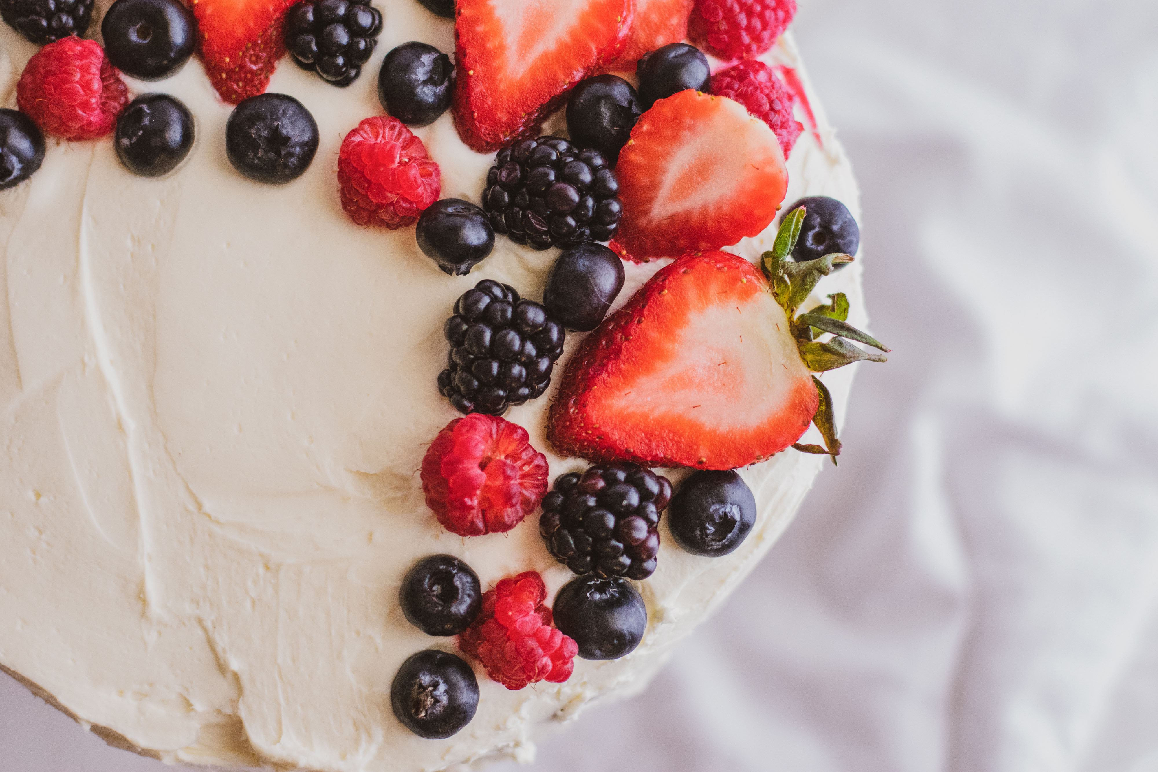Keto Chantilly Cake a white cake with berries covering the top on a cake stand with a white surface