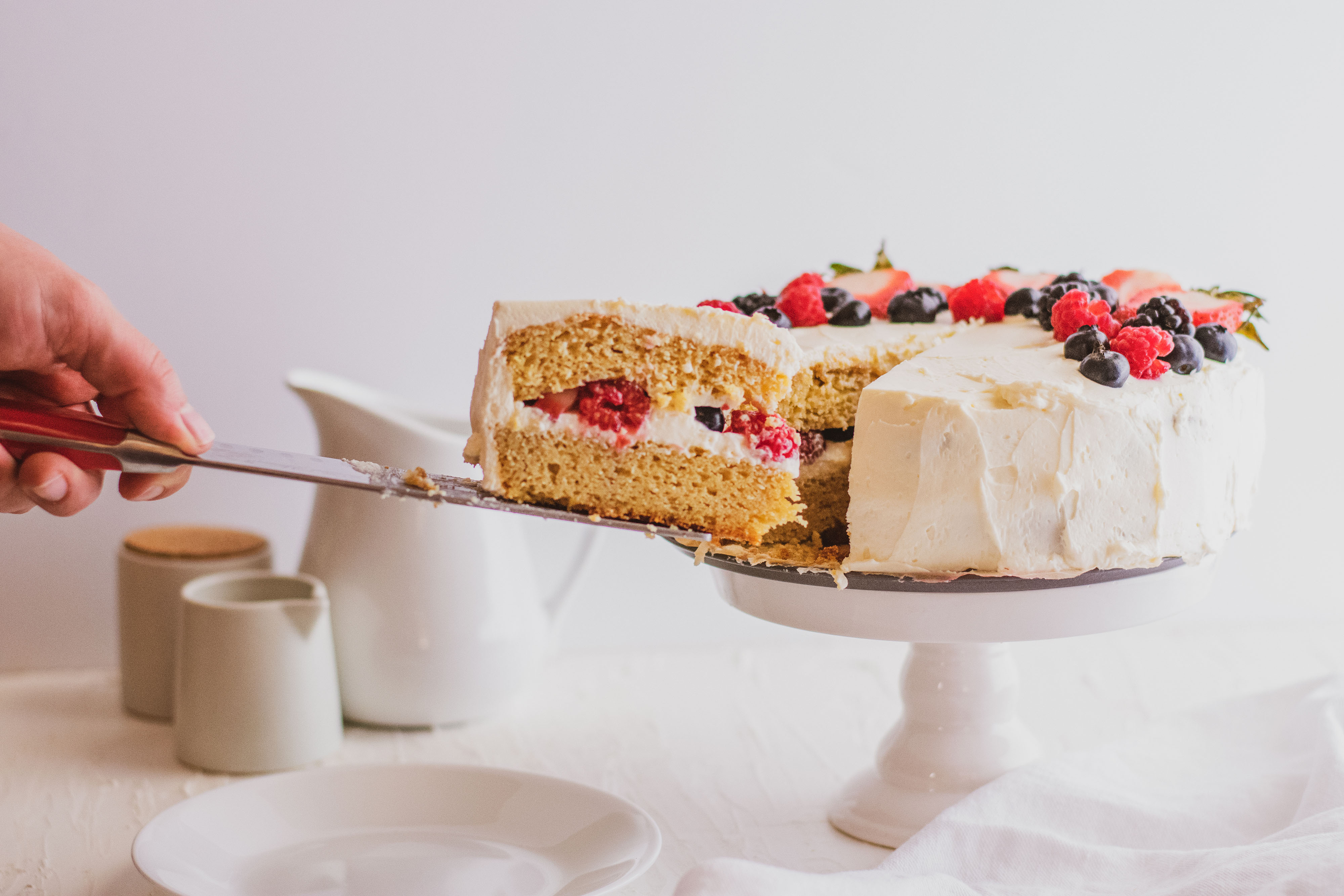 Keto Chantilly Cake a white cake with berries covering the top on a cake stand with a white background and a cut slice being pulled away