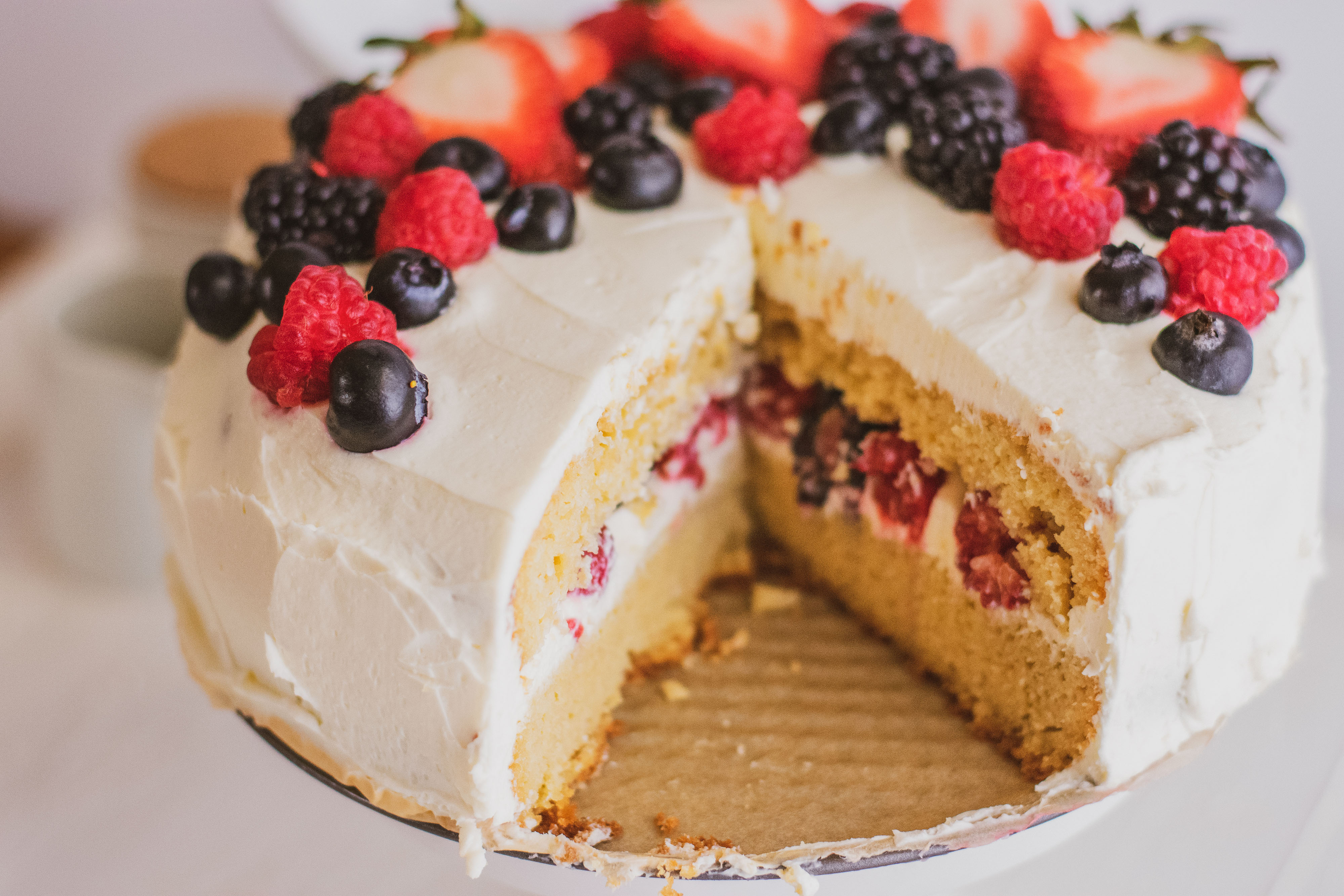 Keto Chantilly Cake a white cake with berries covering the top on a cake stand with a white background and slices taken out of the cake