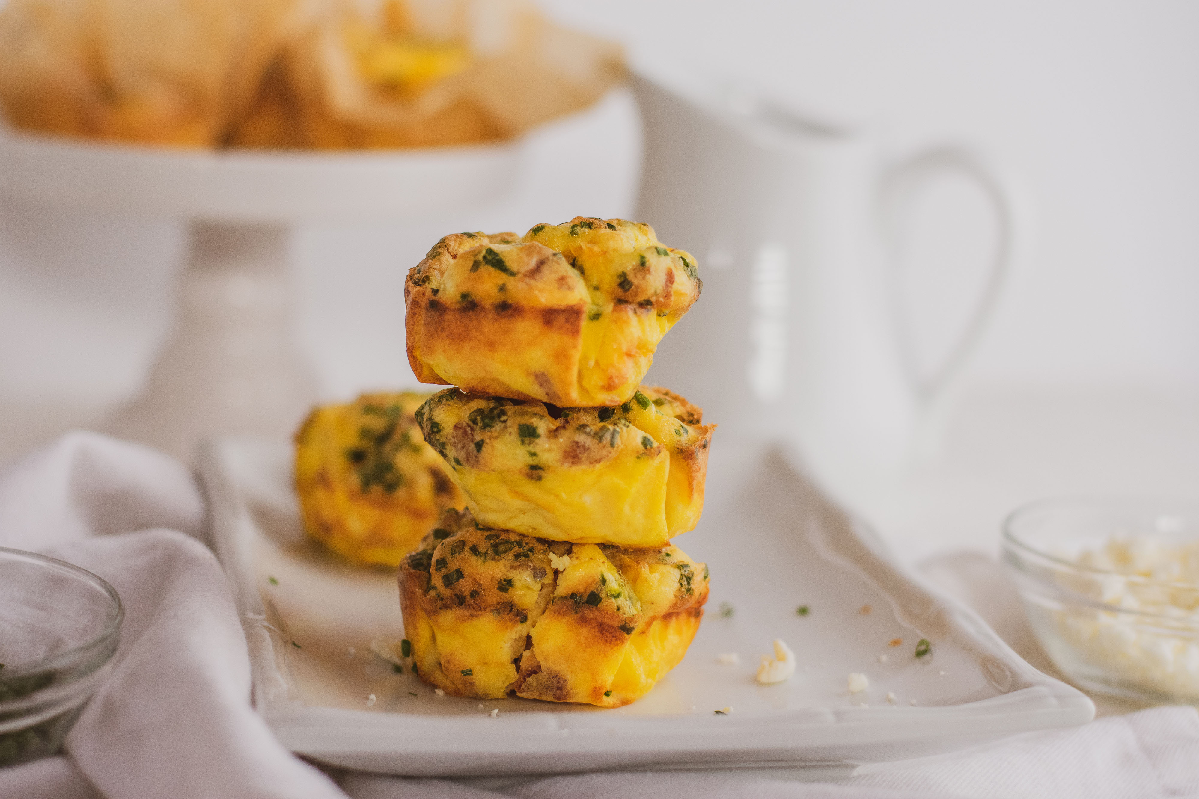 Keto breakfast muffins stacked on a white plate