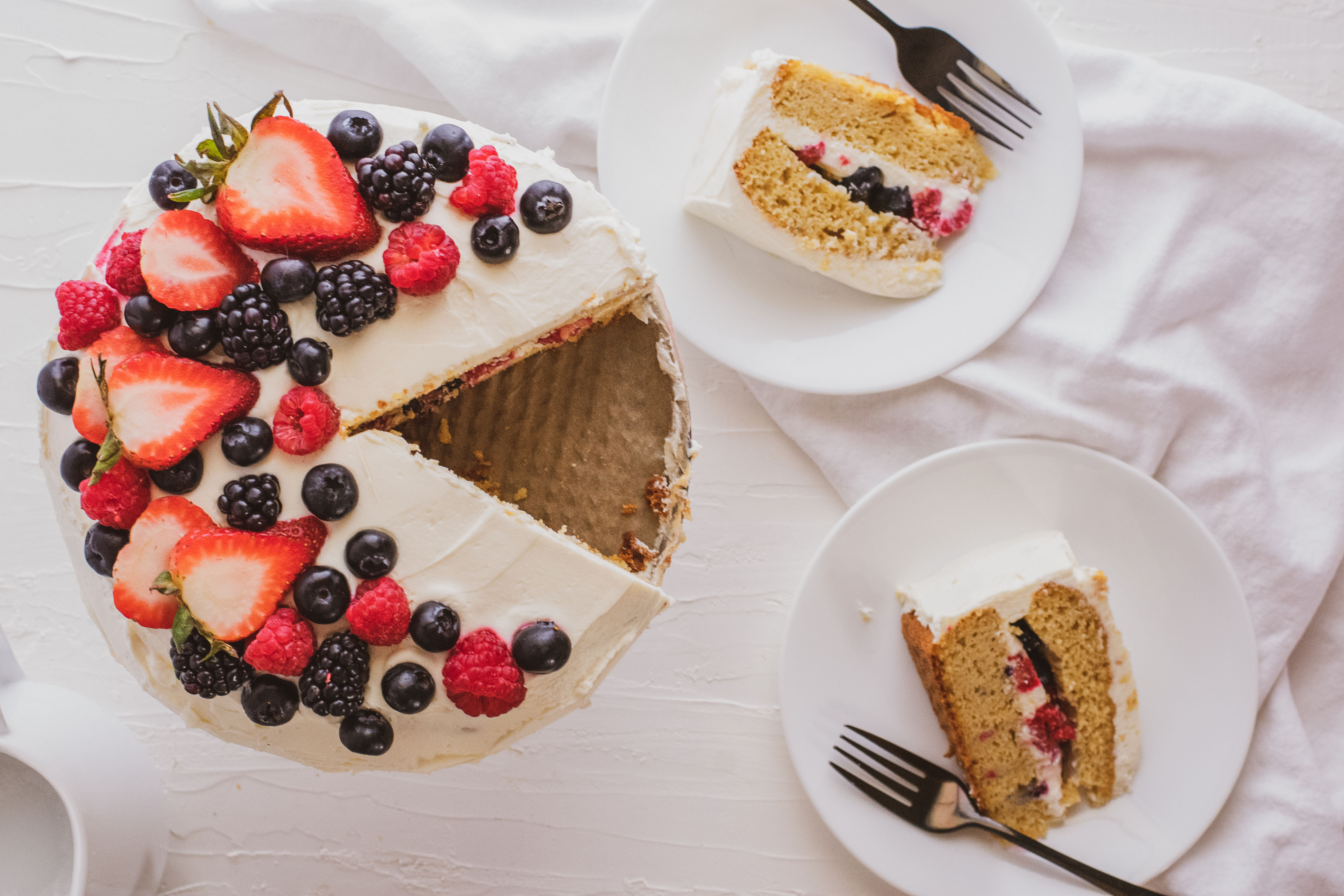 Keto Chantilly Cake a white cake with berries covering the top on a cake stand with a white surface and cut slices on white plates