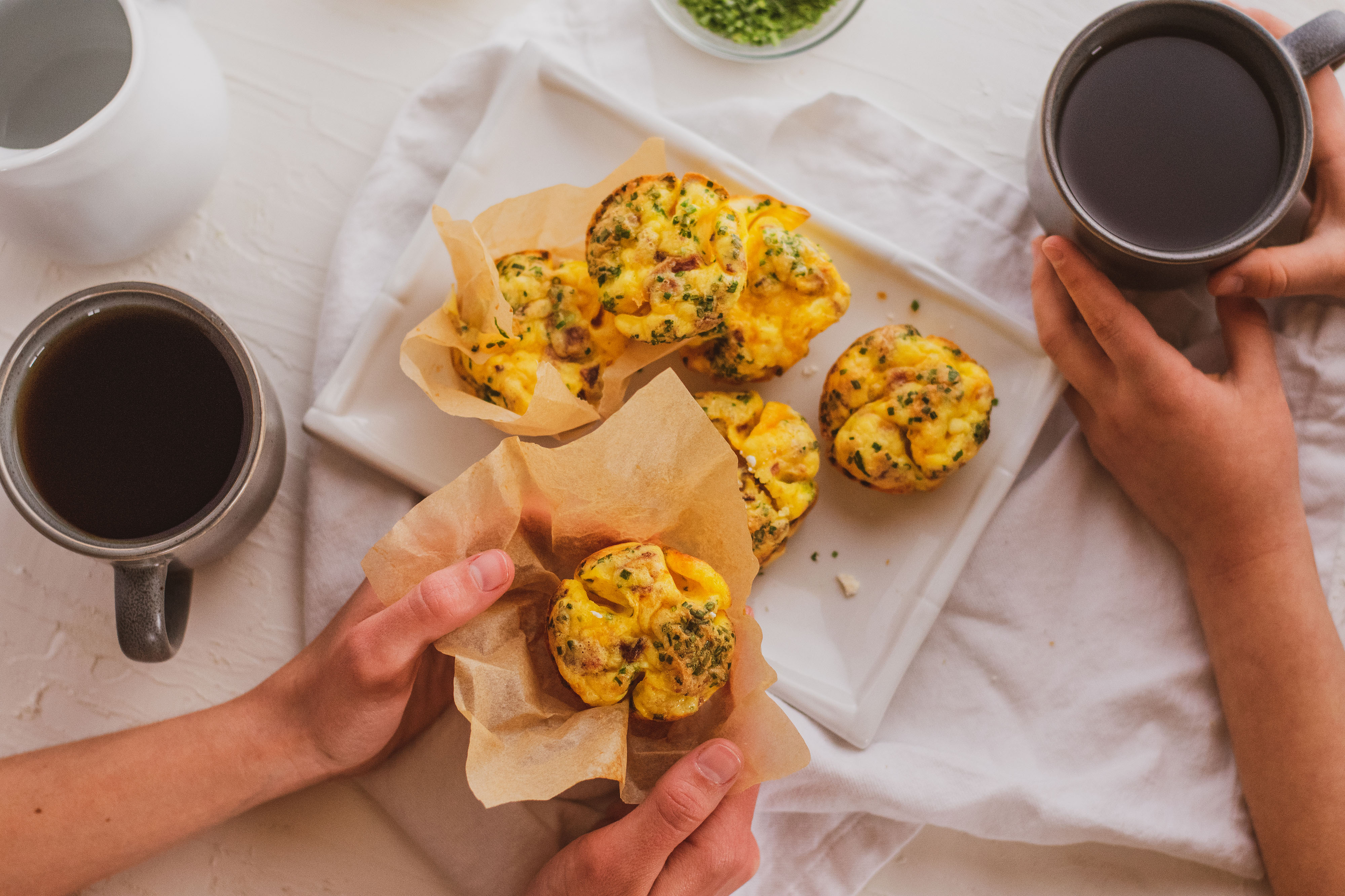 Breakfast muffins on a plate with cups of coffee on the side, and people grabbing some.