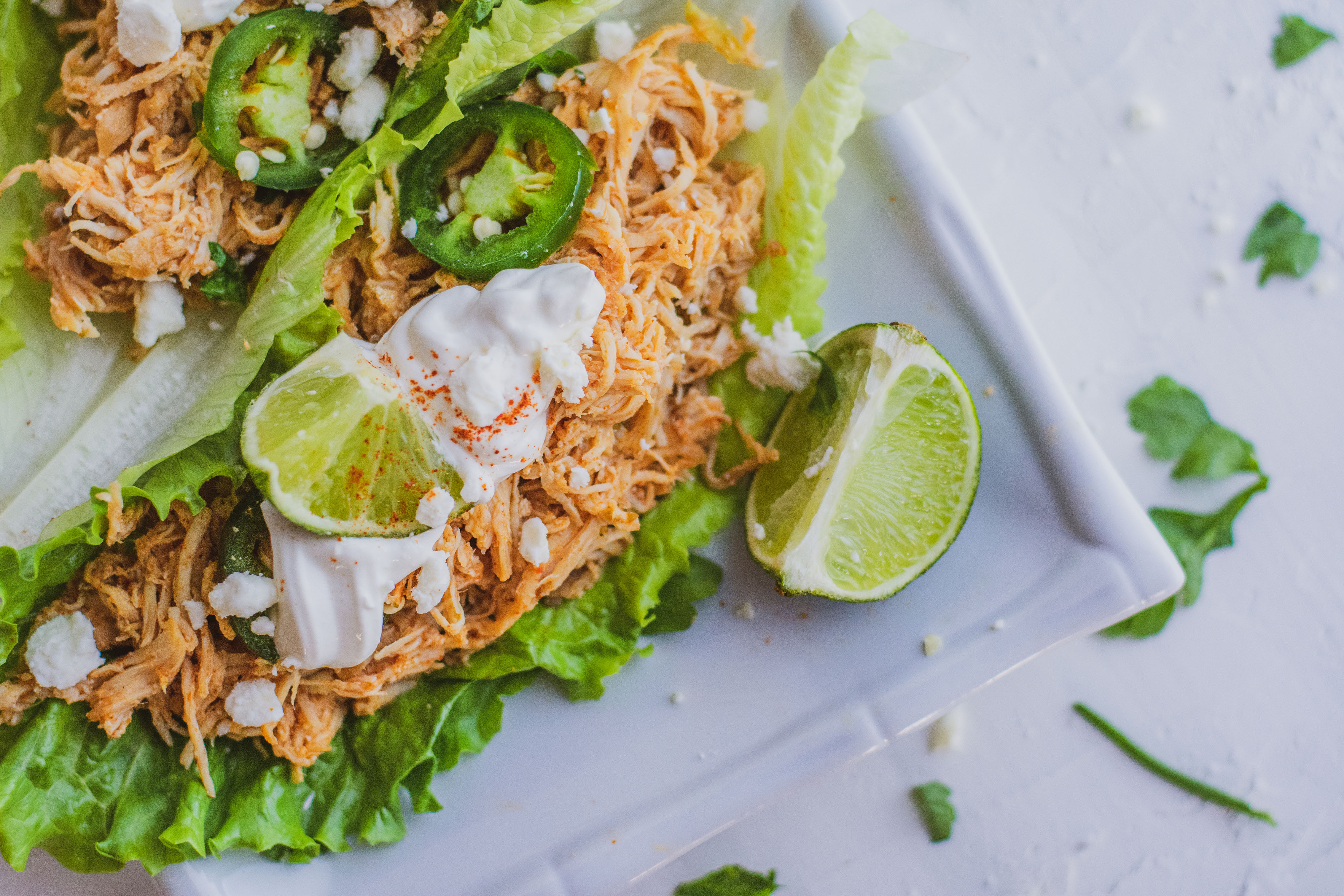 Shredded chicken tacos in lettuce wraps with fetta cheese, limes and jalapenos on top