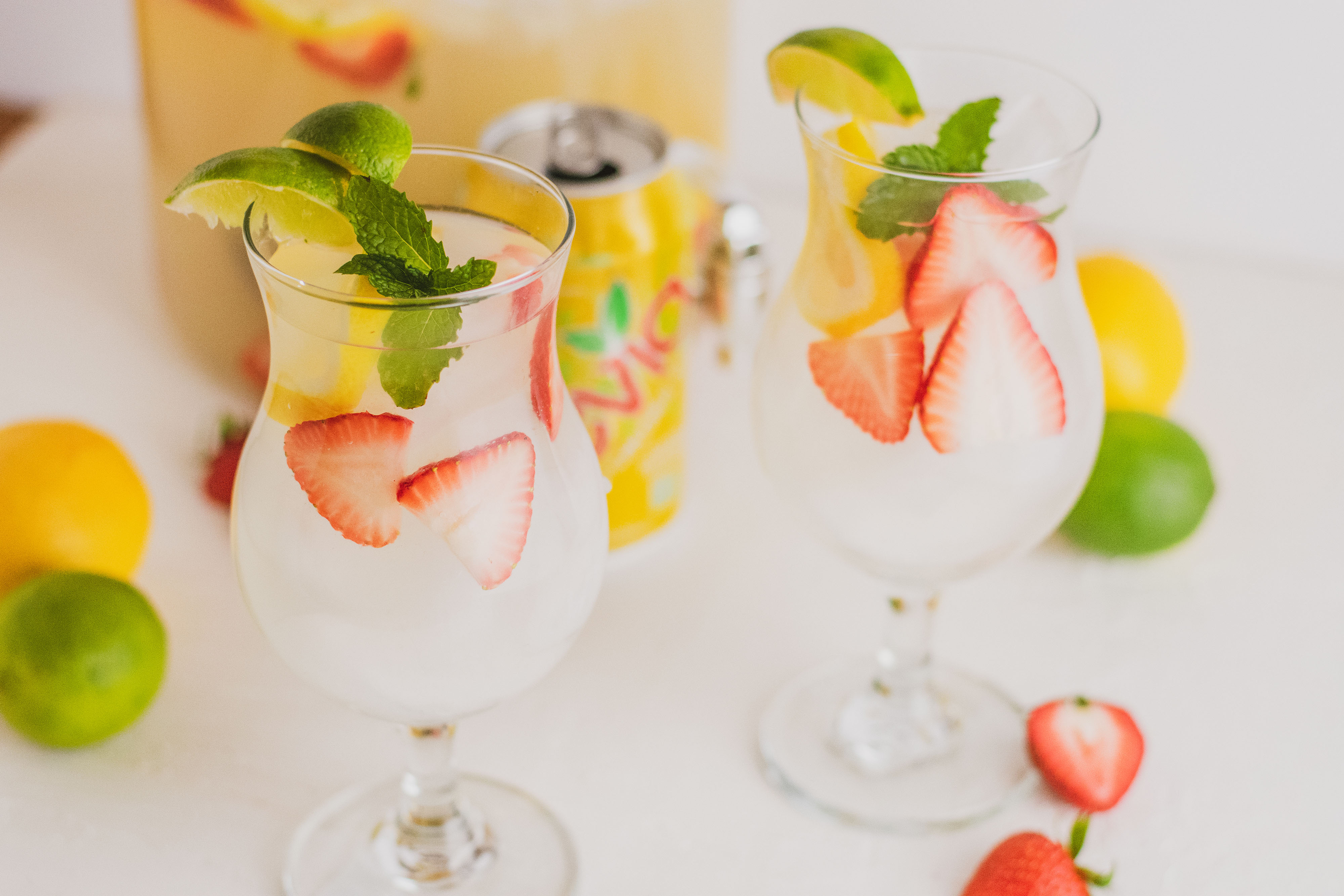 Two glasses with low carb strawberry lemonade mojito drink. With sliced strawberries and lemons and mint leaves on a white surface.