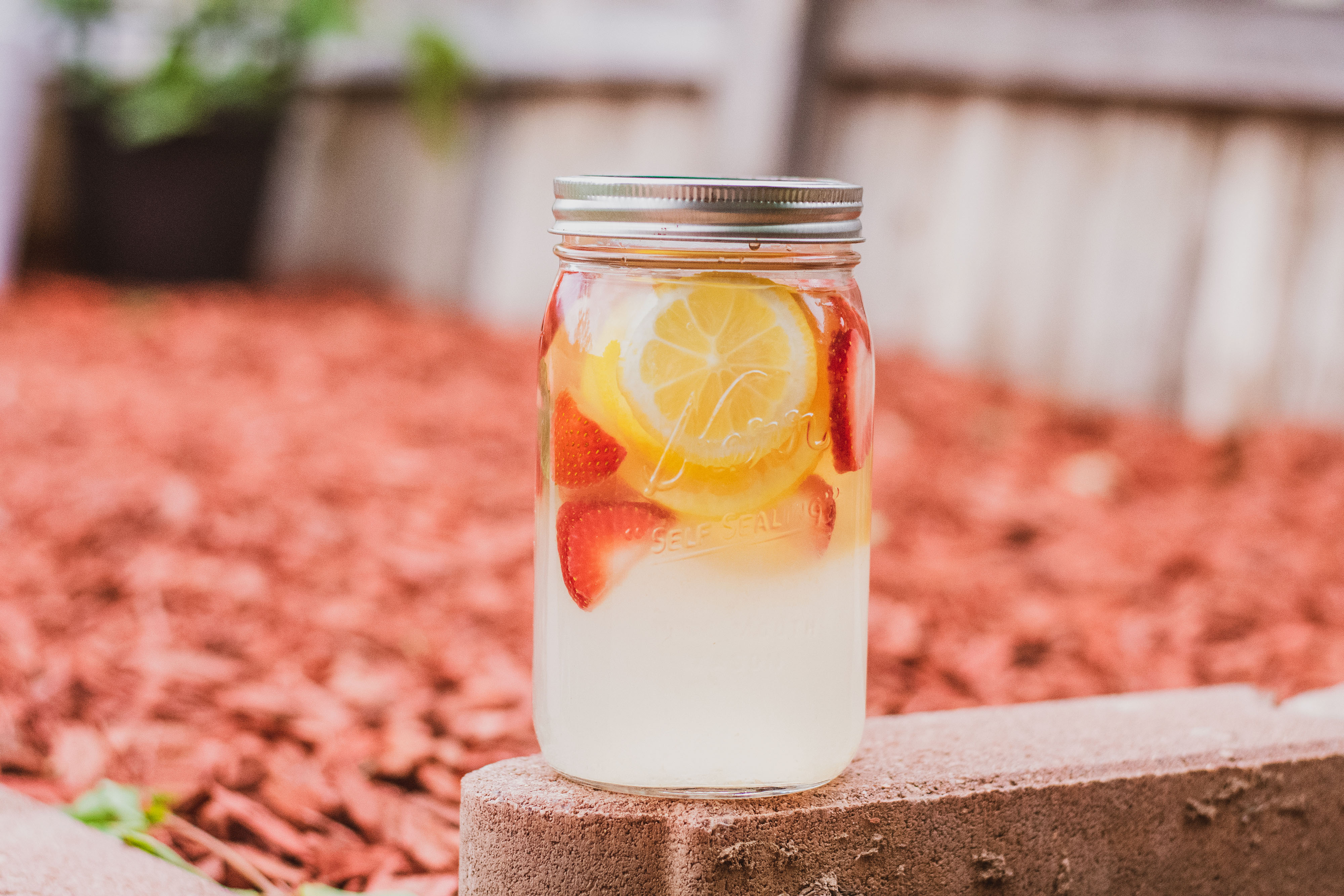A mason jar with low carb strawberry lemonade mojito drink. With sliced strawberries and lemons and mint leaves on a brick.