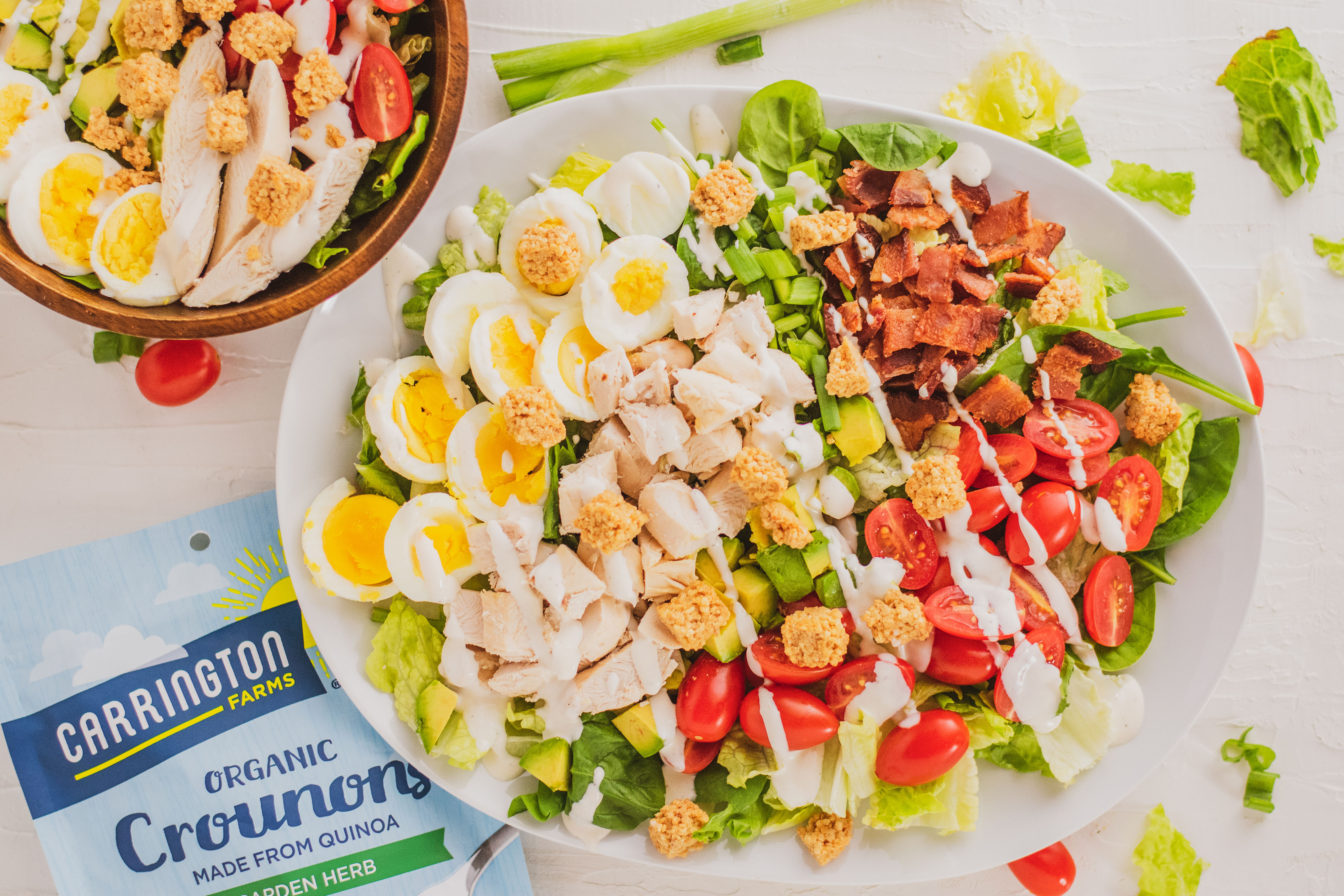 Keto Cobb Salad with sliced boiled egg, sliced chicken, avocado and ranch on top on a white plate with a fork on the side on a white surface.
