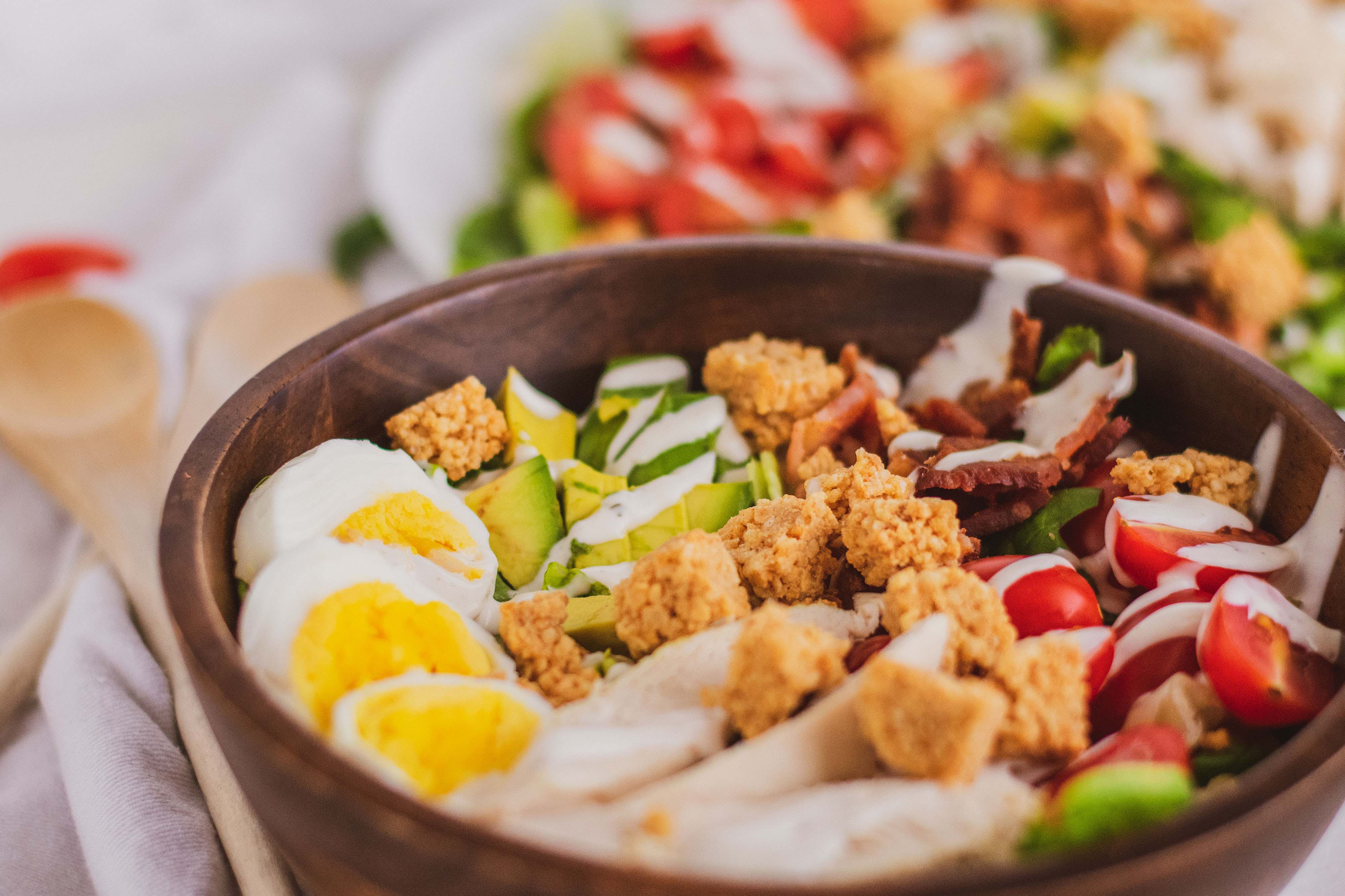 Keto Cobb Salad with sliced boiled egg, sliced chicken, avocado and ranch on top in a bowl with a fork on the side on a white surface.