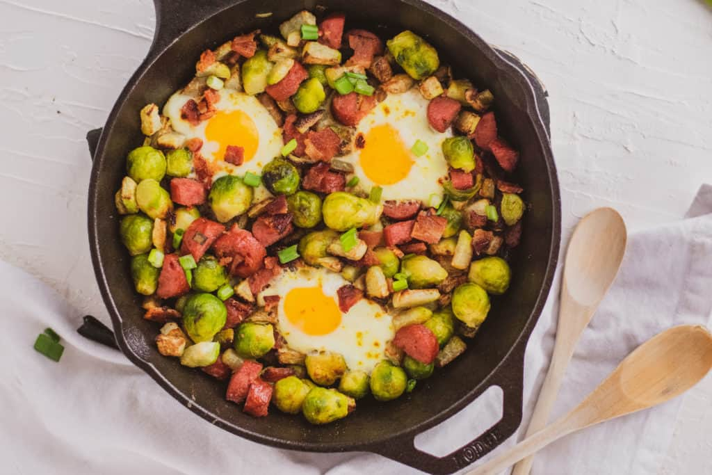 Keto Egg Bake in a cast iron skillet on a white suraface. Loaded with sausage, brussels sprouts and chayote.