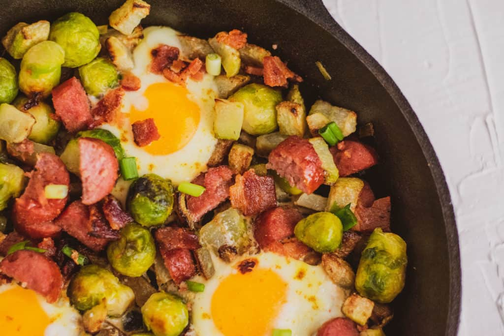Keto Egg Bake in a cast iron skillet on a white surface. Loaded with sausage, Brussels sprouts and chayote.