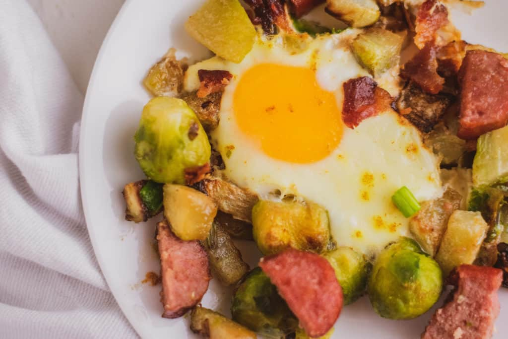 Keto Egg Bake on a white plate with a serving on a white surface. Loaded with sausage, Brussels sprouts and chayote.