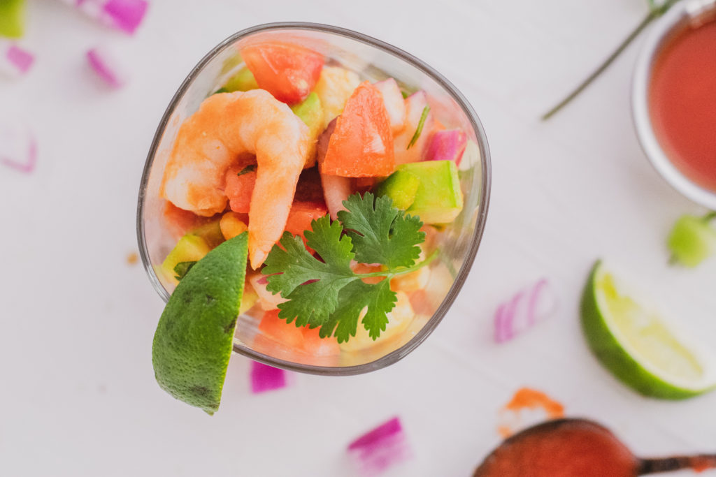 Keto ceviche in a glass cup with a lime on the side on a white surface.