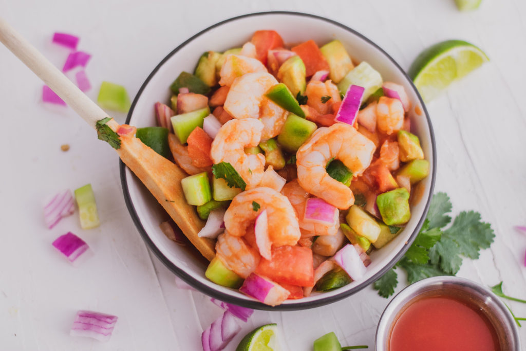 Keto ceviche in a bowl on a white surface.