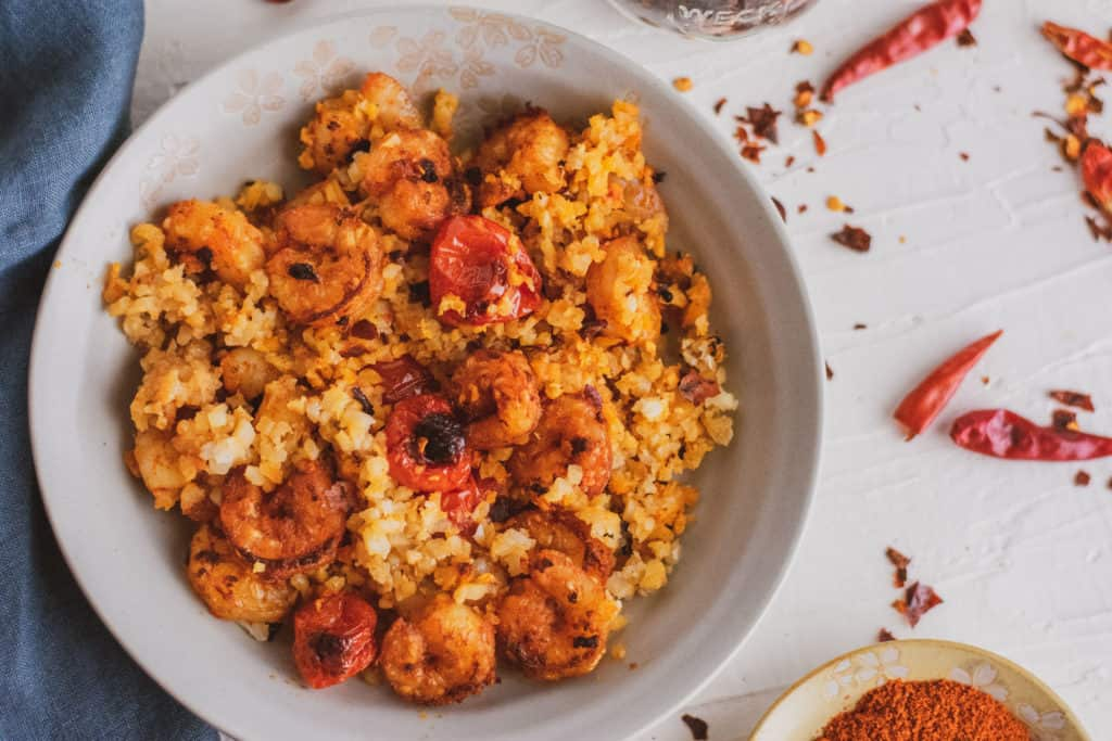 Keto Cajun Shrimp with roasted cherry tomatoes and cauliflower rice in a white bowl on a white surface with chili peppers on the surface.