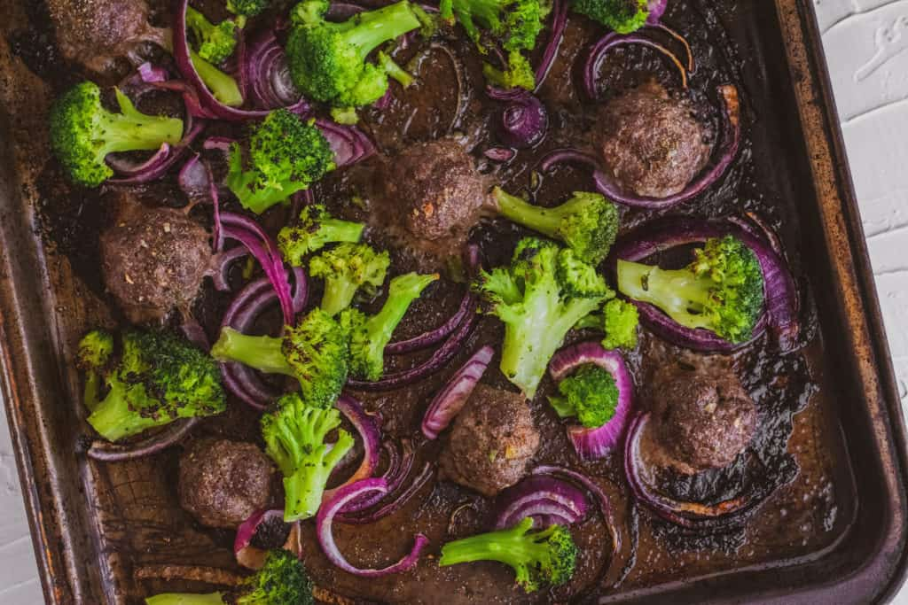 Low carb keto meatballs with a creamy avocado sauce on a sheet pan on a white surface and roasted broccoli and red onions