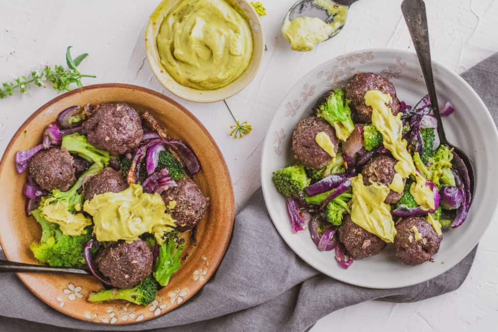 Low carb keto meatballs with a creamy avocado sauce in a bowl on a white surface with a black spoon and roasted broccoli and red onions