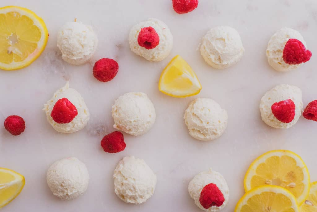 Keto creamy lemon fat bombs with raspberries and lemon slices on a white surface