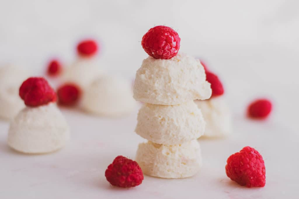 Keto creamy lemon fat bombs with raspberries on a white surface