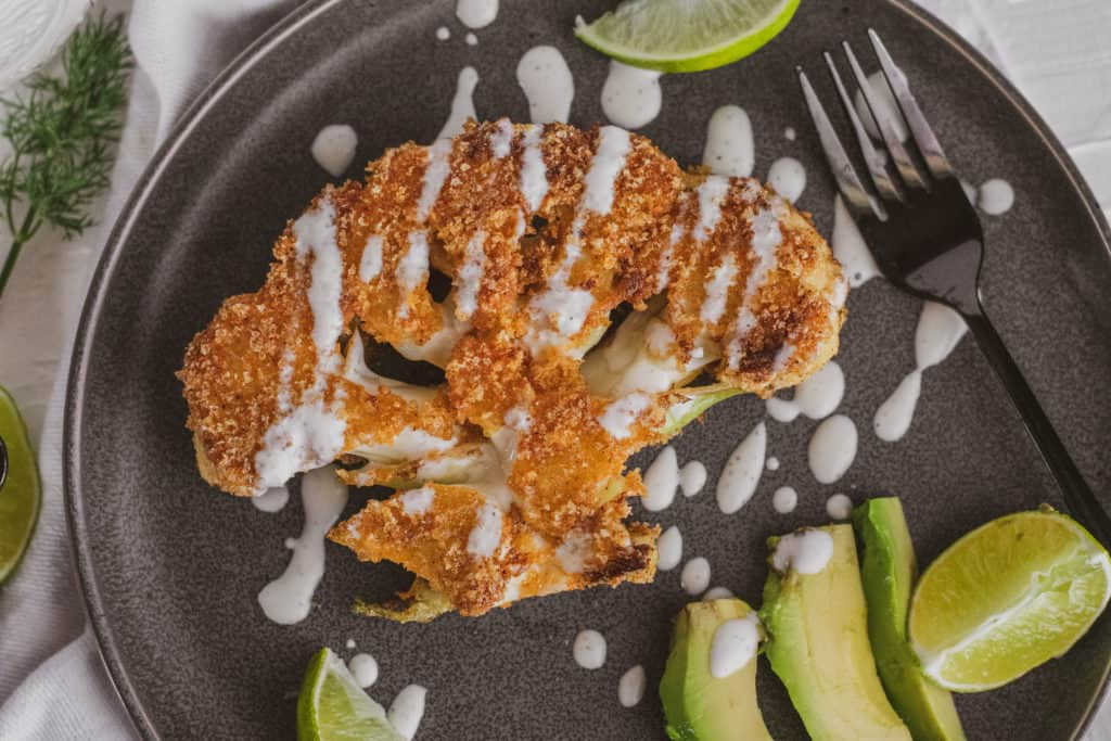 Fried pork rind covered cauliflower steaks on a grey plate with ranch on top and avocado and limes on the side.