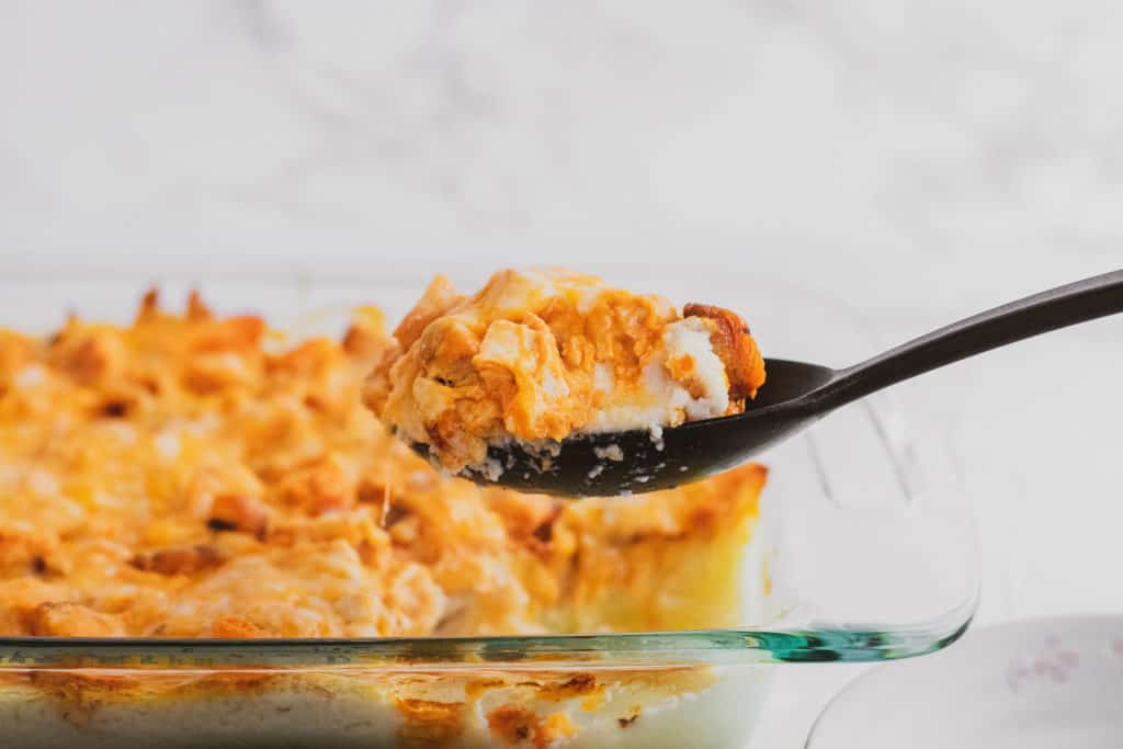 Low carb mashed cauliflower buffalo chicken in a clear casserole dish with a black serving spoon picking up a serving.