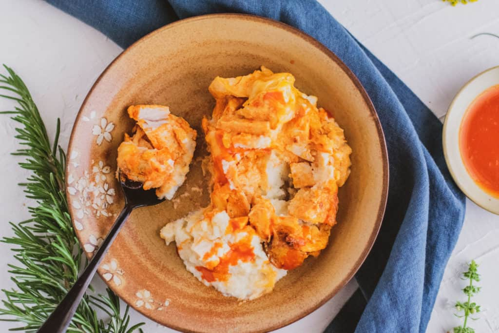 Low carb mashed cauliflower buffalo chicken in a bowl on a white surface with a blue napkin on the side.