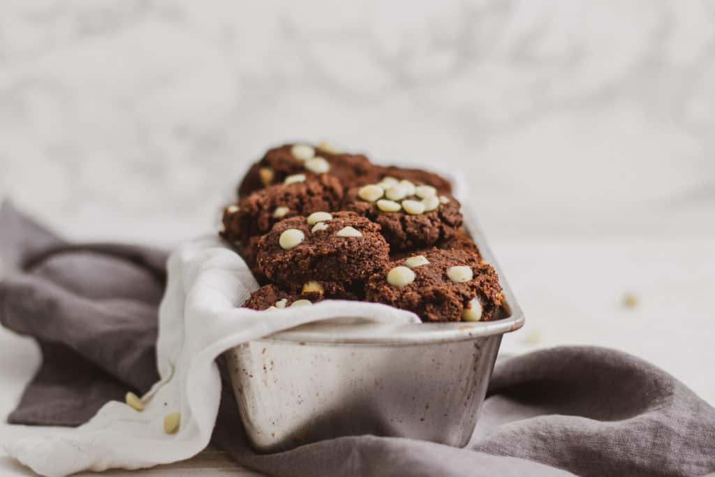 Low carb white chocolate chip chocolate cookies in a bread pan with a white cloth and grey napkin on the side.