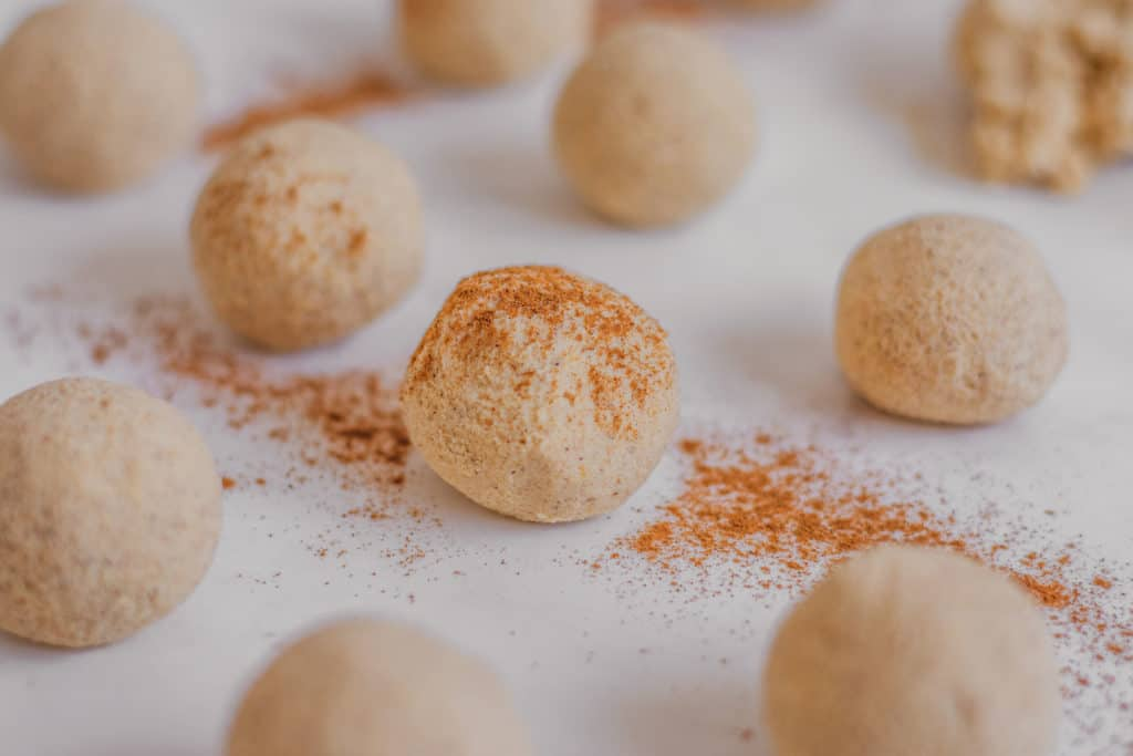 Keto Pumpkin Spice Fat Bombs rolled into balls with cinnamon on top on a white surface.