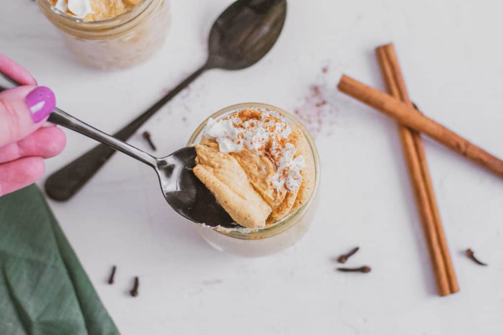 Low carb pumpkin cheesecake mousse in a clear jar with cinnamon sticks, black spoons, and a green linen on the side with a spoon fell being taken out. Keto dessert.