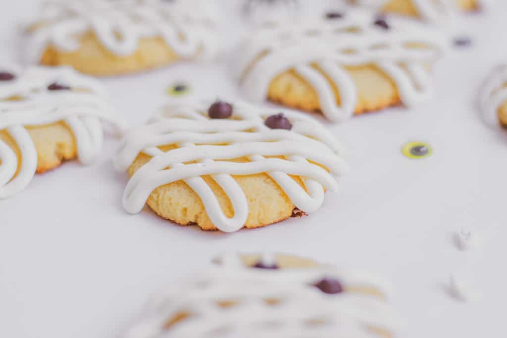 Keto Mummy sugar cookies with cream cheese frosting lines on the cookies and chocolate chip eyes on a white surface.