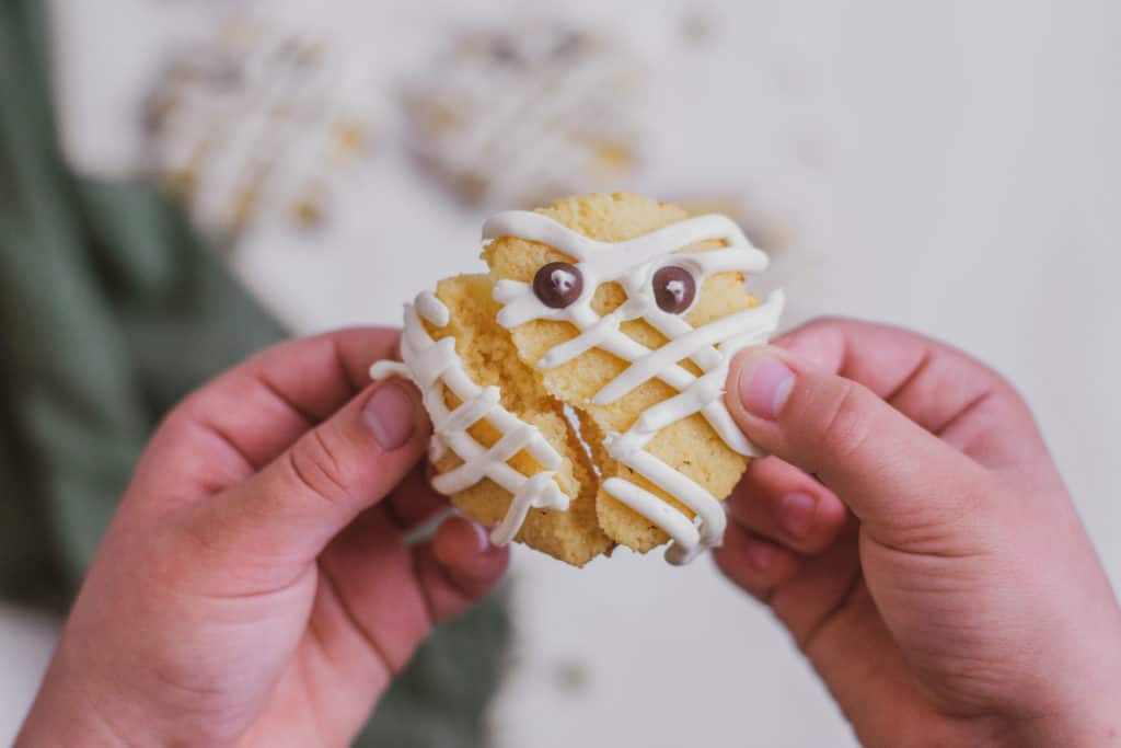 Keto Mummy sugar cookies with cream cheese frosting lines on the cookies and chocolate chip eyes. Being pulled apart by kid hands.