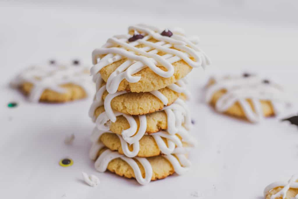 Keto Mummy sugar cookies with cream cheese frosting lines on the cookies and chocolate chip eyes on a white surface stacked on top of each other.