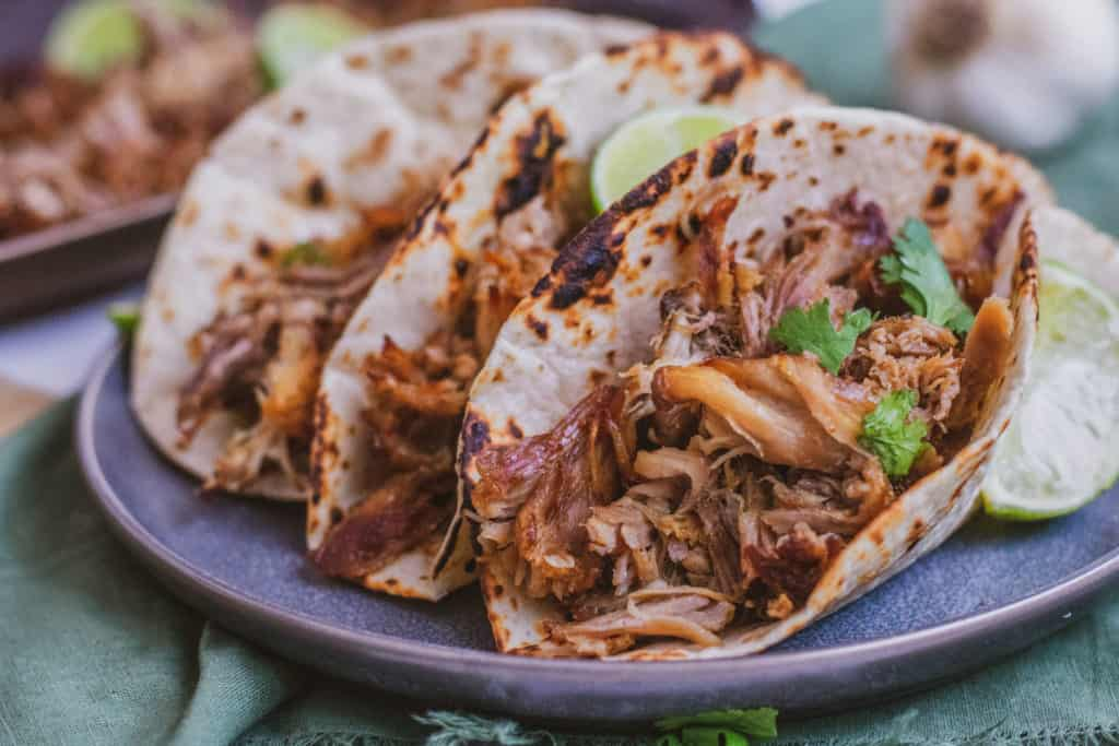 Low carb keto Instant pot pork carnitas in a tortilla on a black plate