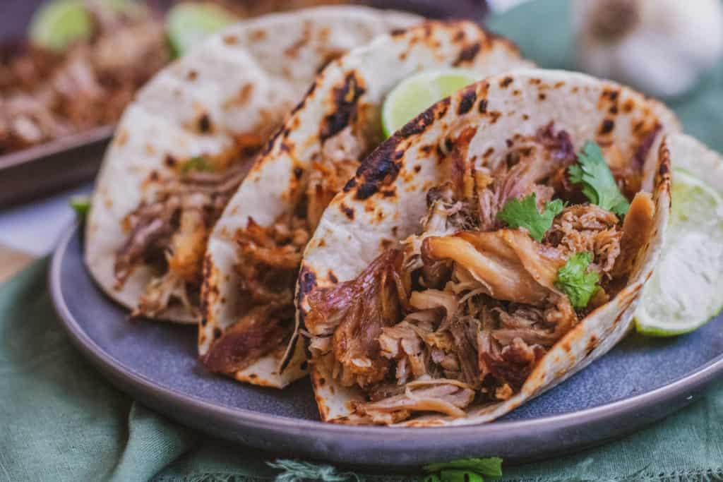 Low carb keto Instant pot pork carnitas in a tortilla on a black plate